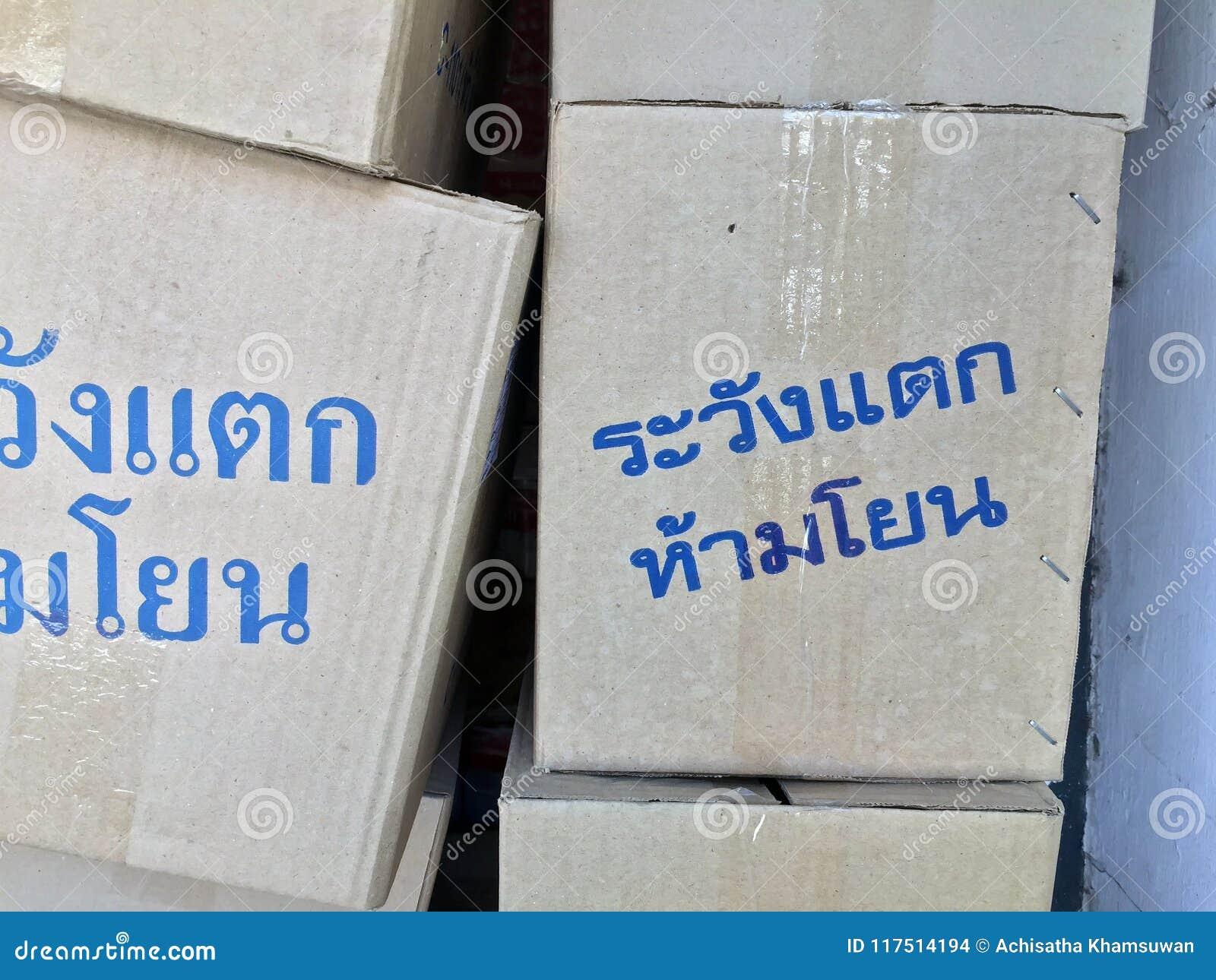 """Pila di scatola di carta, di colore grigio e di colore del blu di testo nella lingua tailandese che """"Warning! Fragile, non fa i"""
