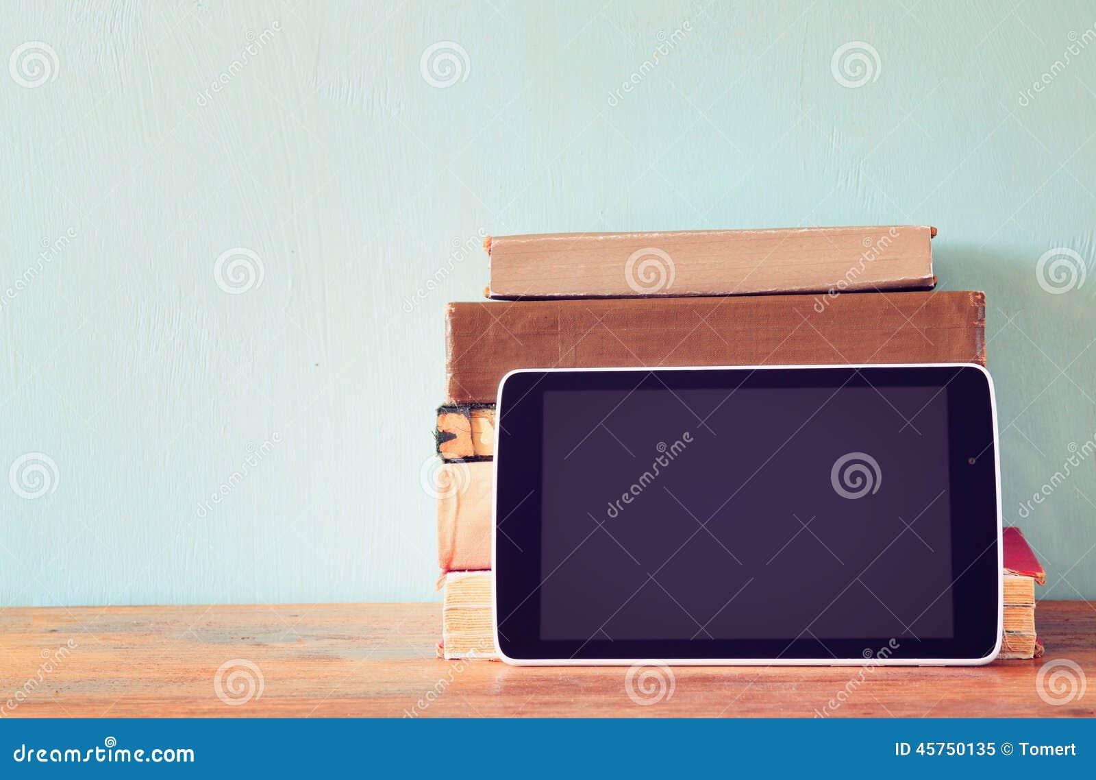 Pila di vecchi libri e di compressa sopra lo scaffale di legno Concetto di nuova tecnologia Stanza per testo