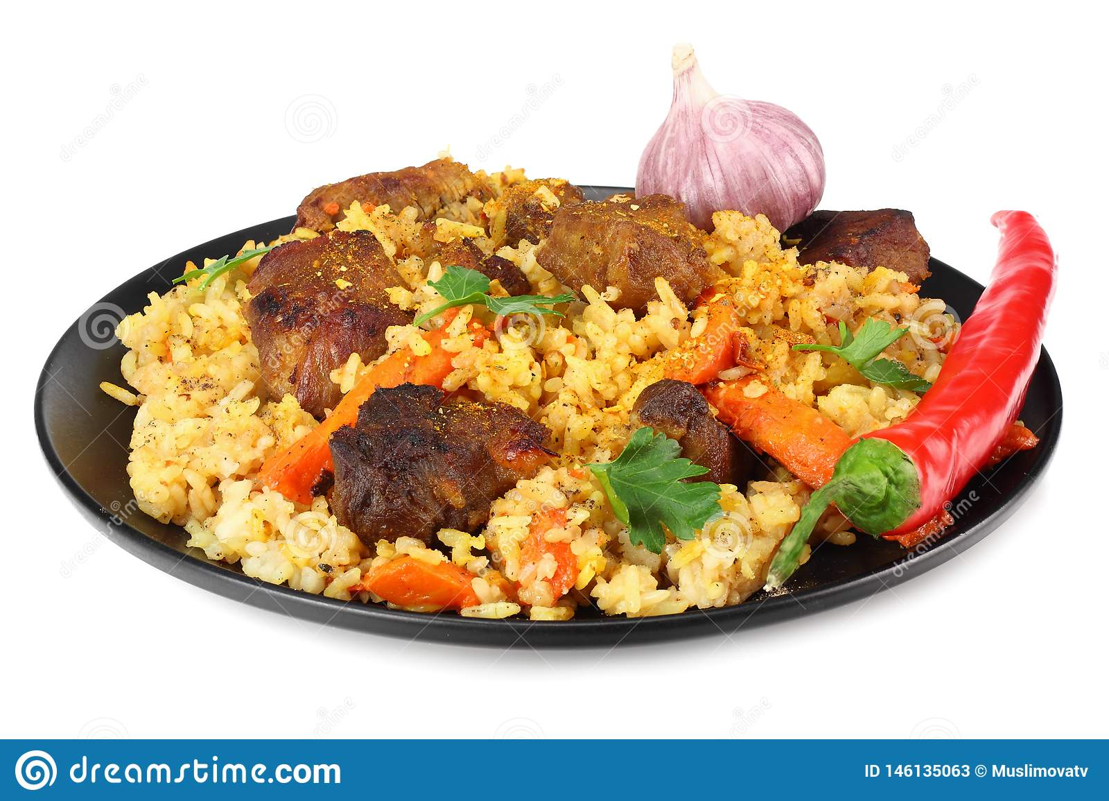 pilaf with meat and chili pepper on black plate isolated on white background