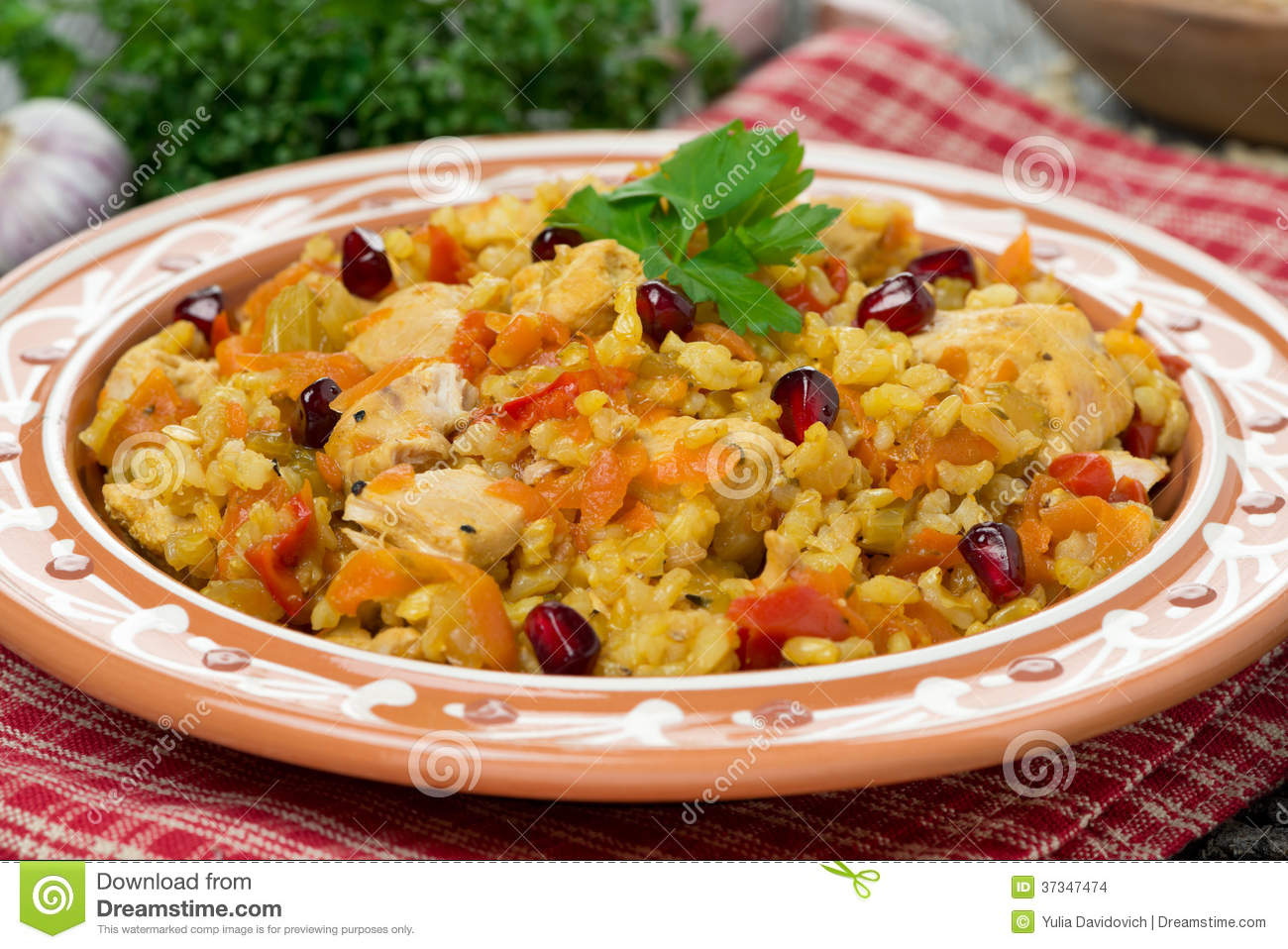 Pilaf with vegetables, chicken and pomegranate, close-up