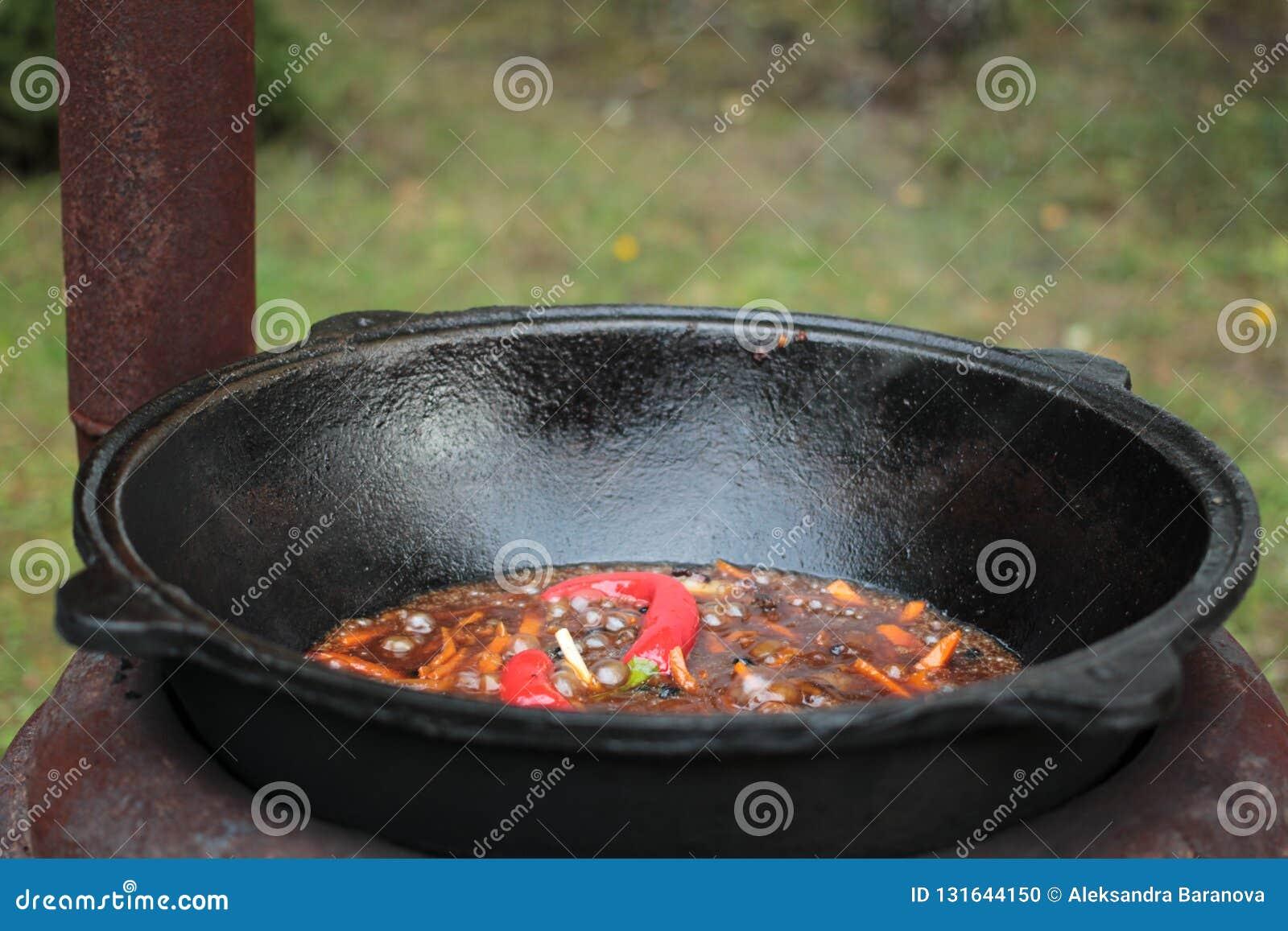 Pilaff förbereder sig i stort svart gjutjärn med kockar räcker
