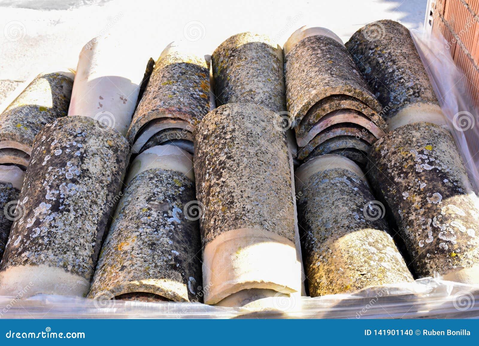 Pilas de tejas de tejado viejas en muchas filas con diverso número en cualquier columna Las tejas antiguas se manchan con polvo y