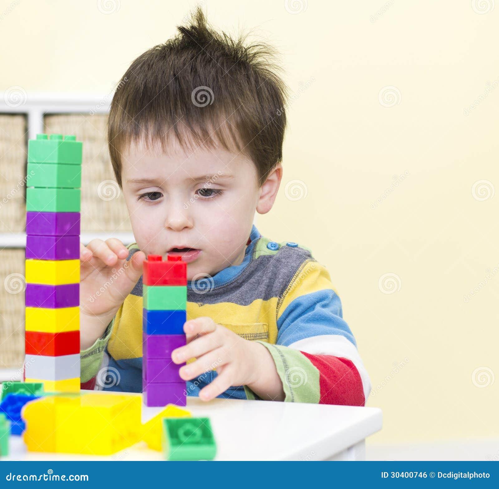 Pilas jovenes del muchacho que conectan bloques
