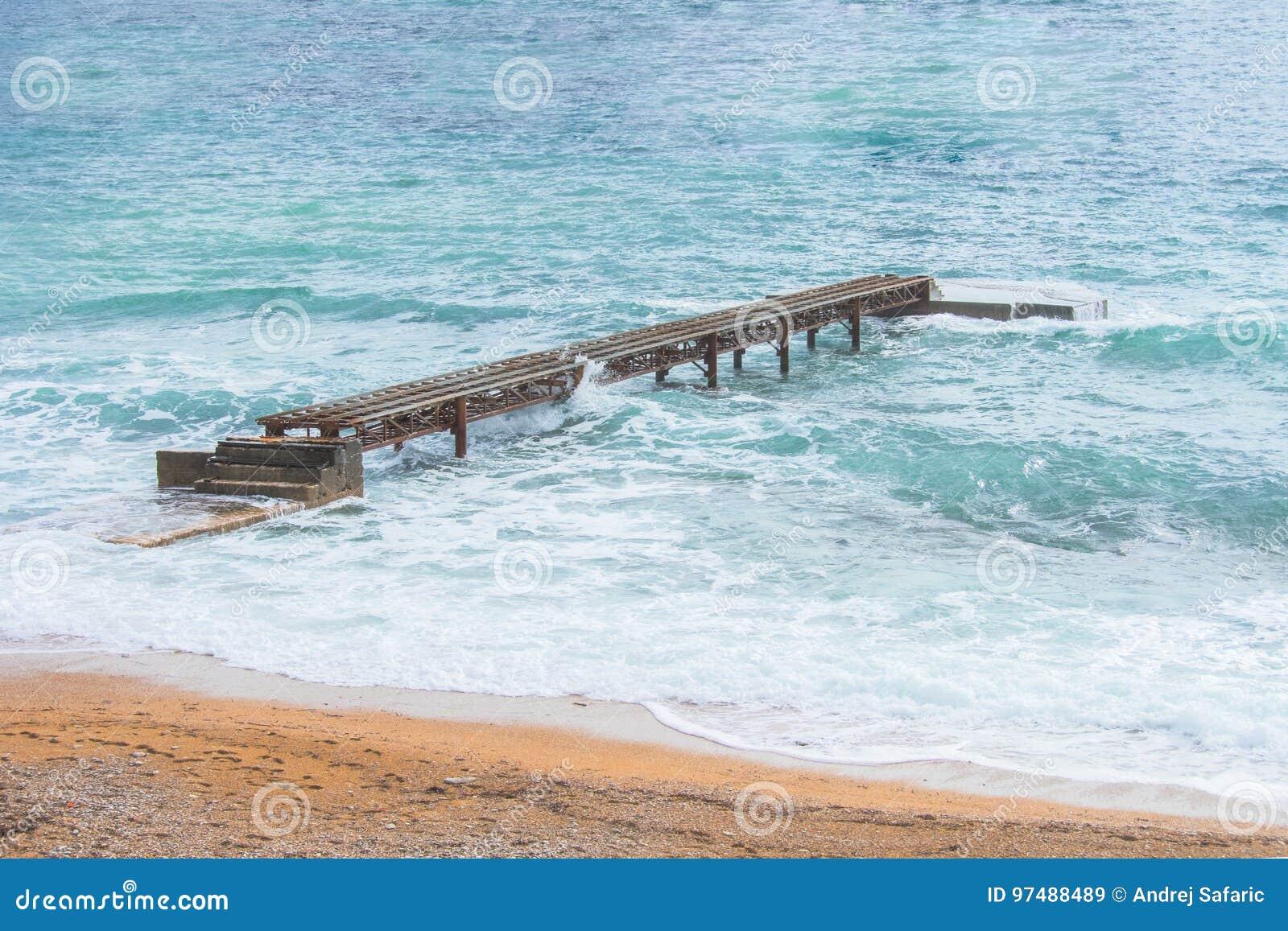 Pilastro arrugginito sui precedenti del mare e delle onde