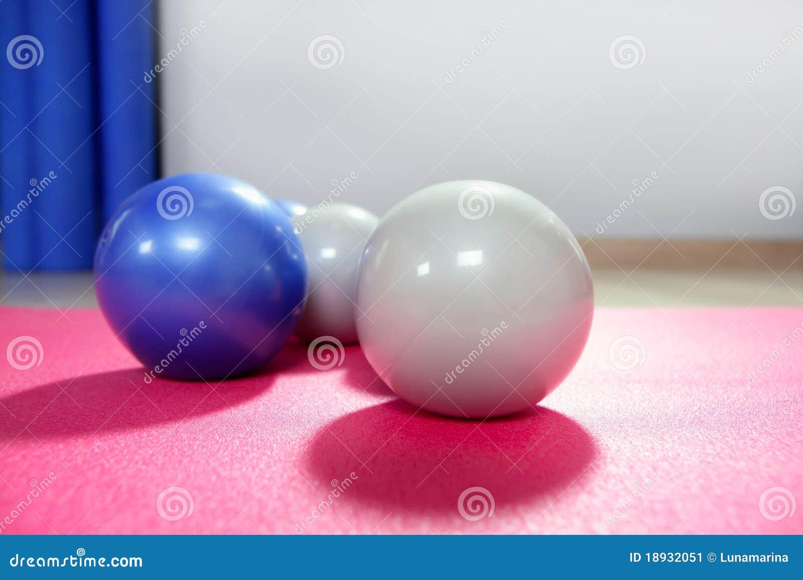 Pilates che modifica le sfere la tonalità sopra la stuoia rossa di yoga