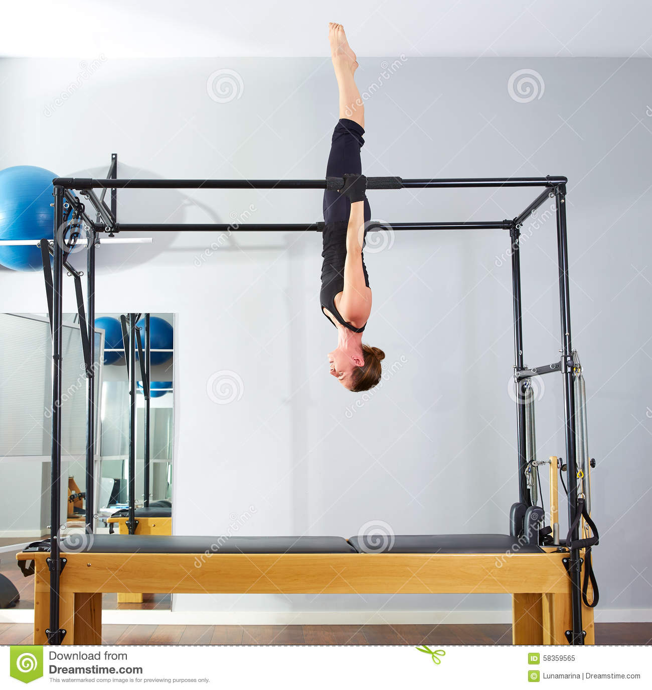 Pilates Woman In Cadillac Acrobatic Upside Down Stock Photo - Image: 58359565