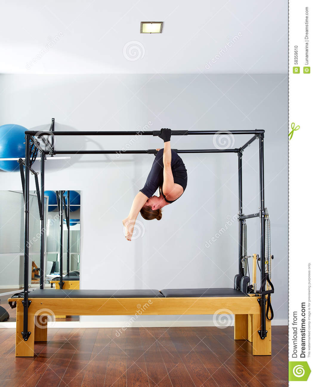 Cadillac Pilates: Pilates Woman In Cadillac Acrobatic Upside Down Stock Photo