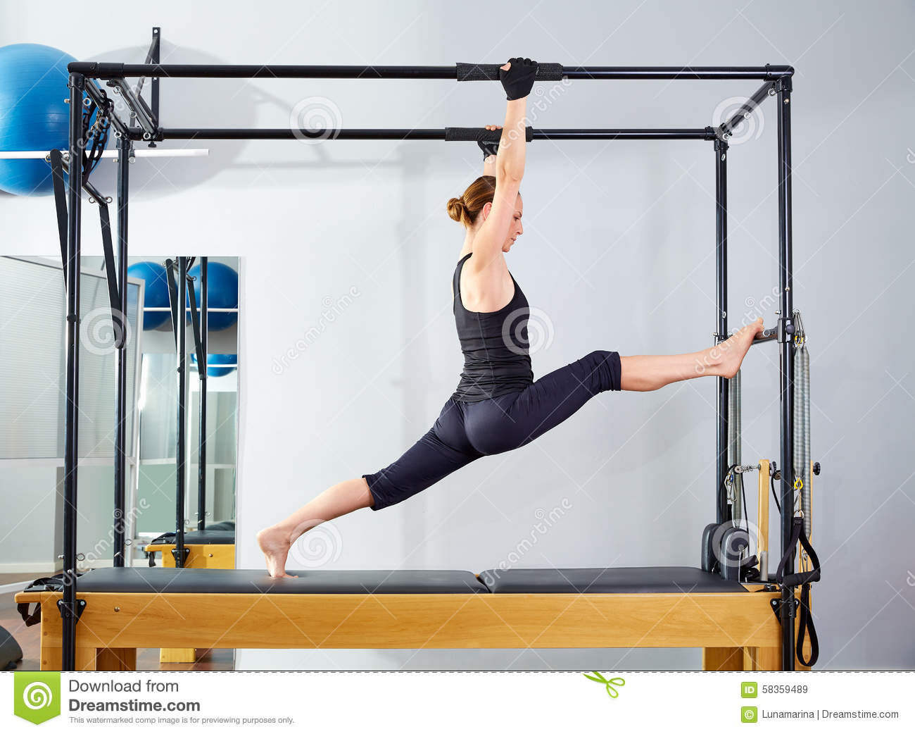 Pilates woman in cadillac legs split reformer stock photo for Gimnasio pilates