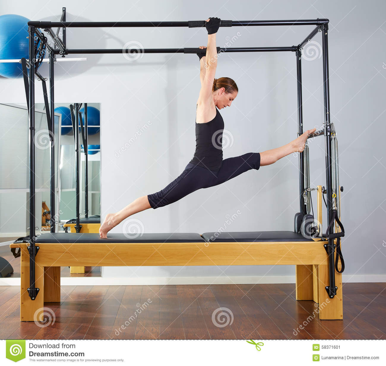 Cadillac Pilates: Pilates Woman In Cadillac Legs Split Reformer Stock Image