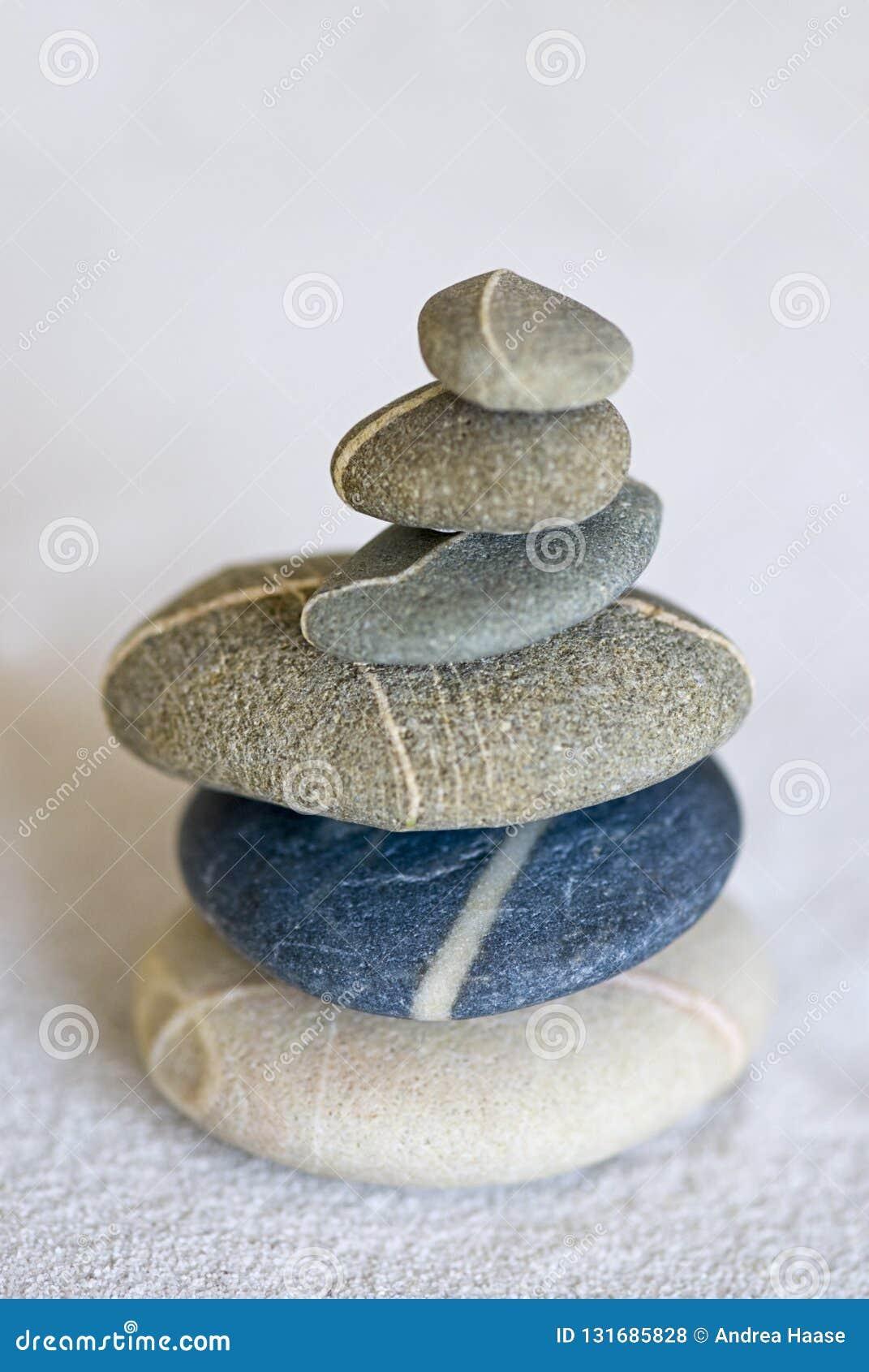 Pile équilibrée de caillou lisse dans une cuvette en bambou