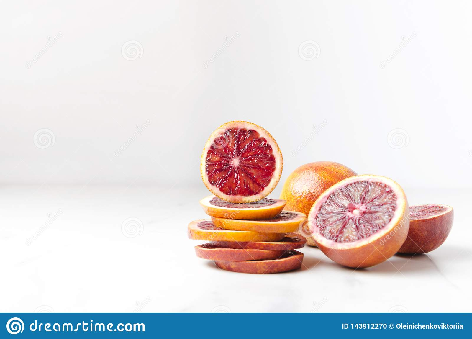 Pile of blood orange slices and halfs of it on the white table.Empty space for your design