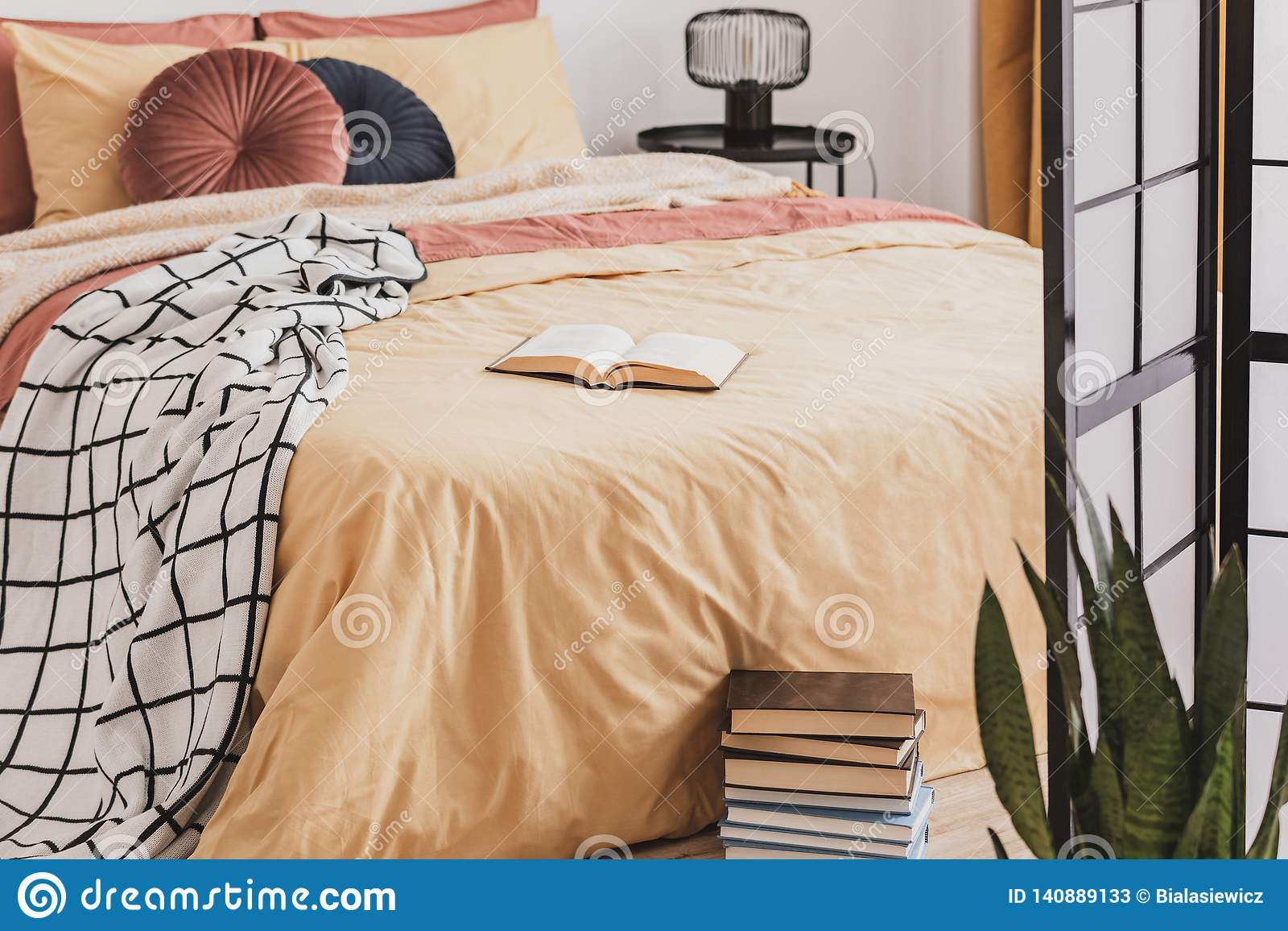 Foot Of The Bed pile of books in foot of king size bed with yellow duvet and