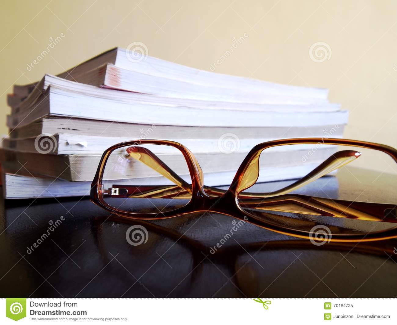 Pile of books and a pair of eyeglasses