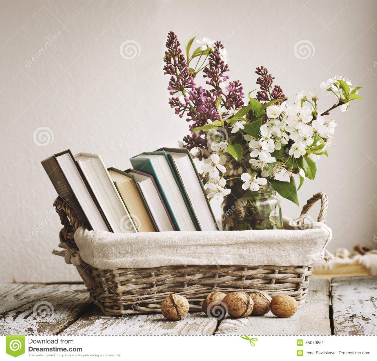 Pile of books and spring flowers of a lilac and apricot in for Decoration books