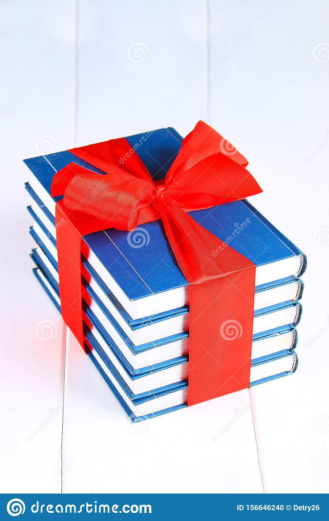 A pile of books tied with a red ribbon on a white wooden table