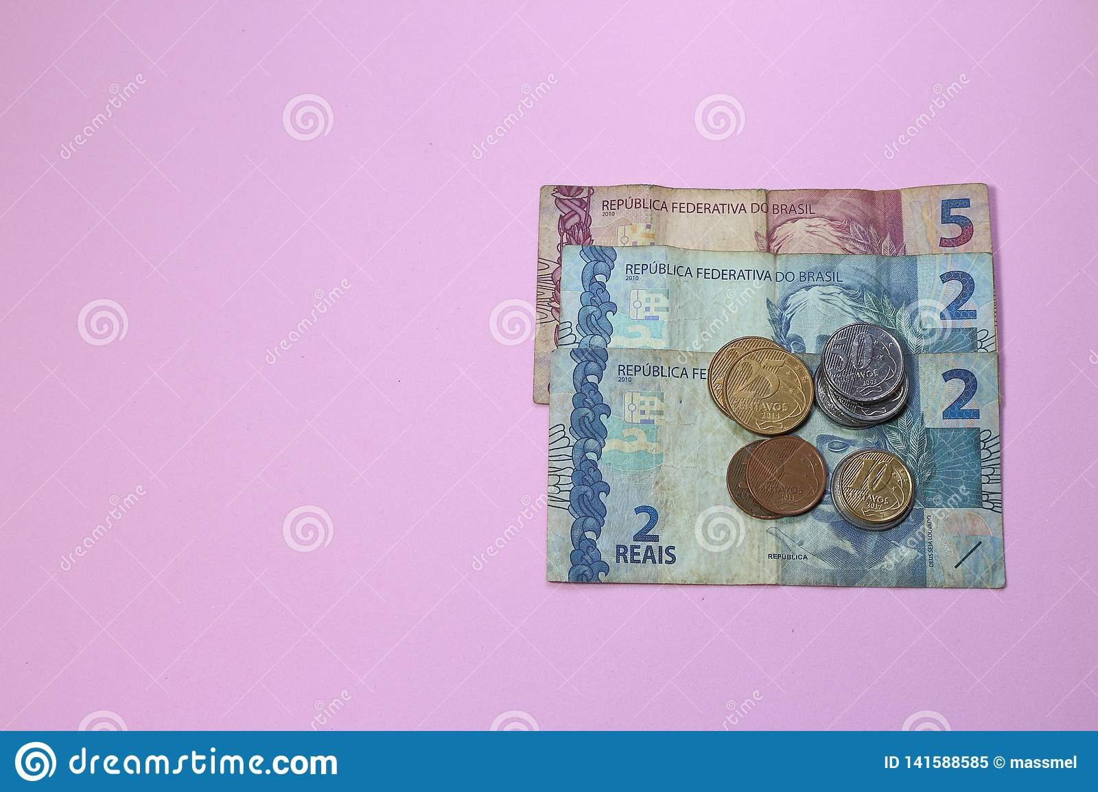 Pile of brazilian money low value on pink background with copy space for text.