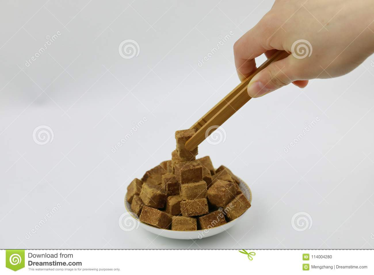 A pile of brown sugar cubes on a white plate woman hand hold wooden tweezers on white background