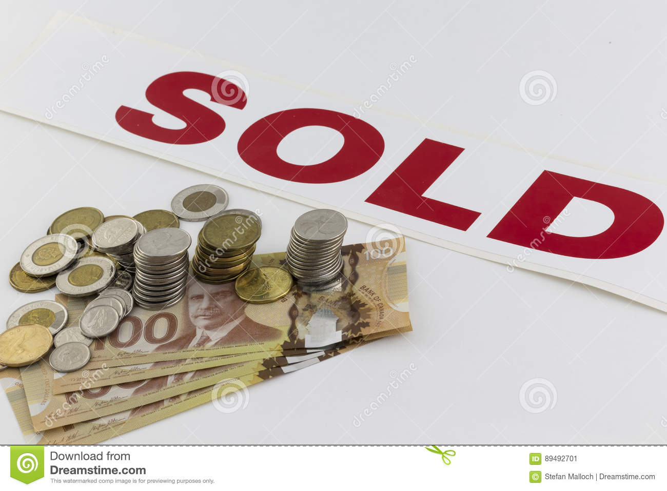 Pile of Canadian money with sold sign