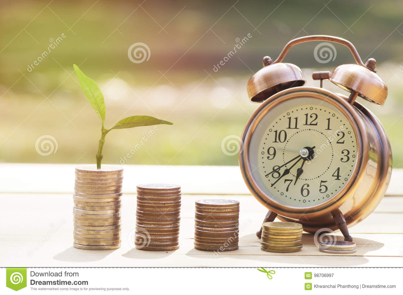 pile of coins and small tree with alarm clcok