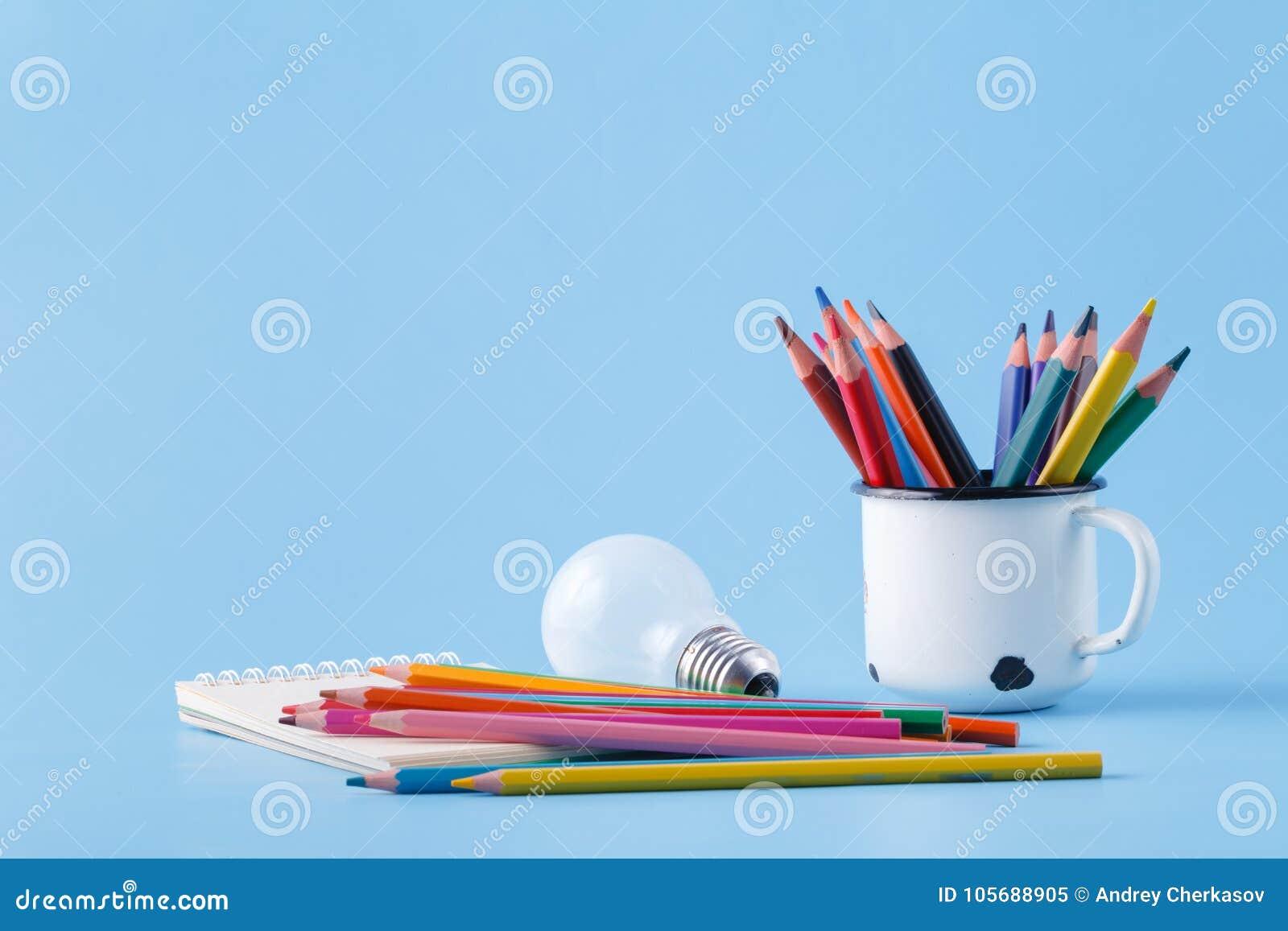 Pile of colour pencils on light blue background, creative idea c