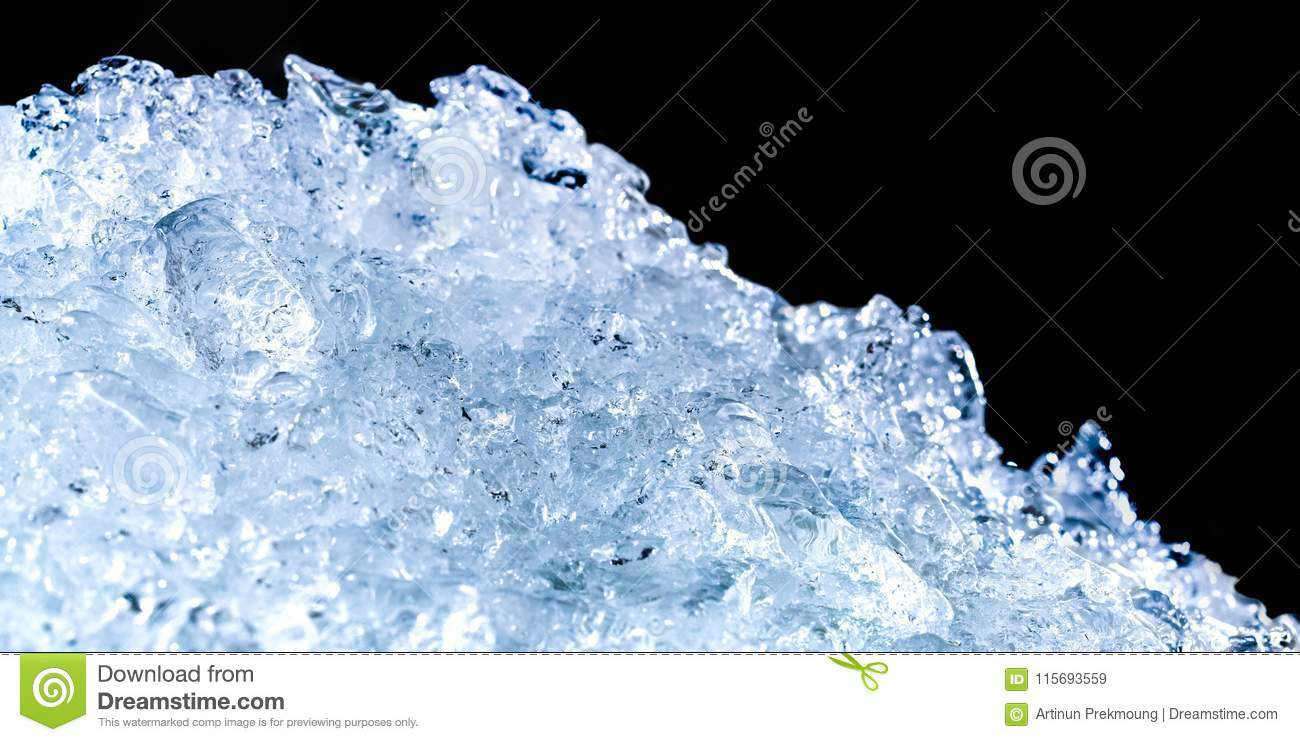 Pile of crushed ice cubes on dark background with copy space. Crushed ice cubes foreground for beverages