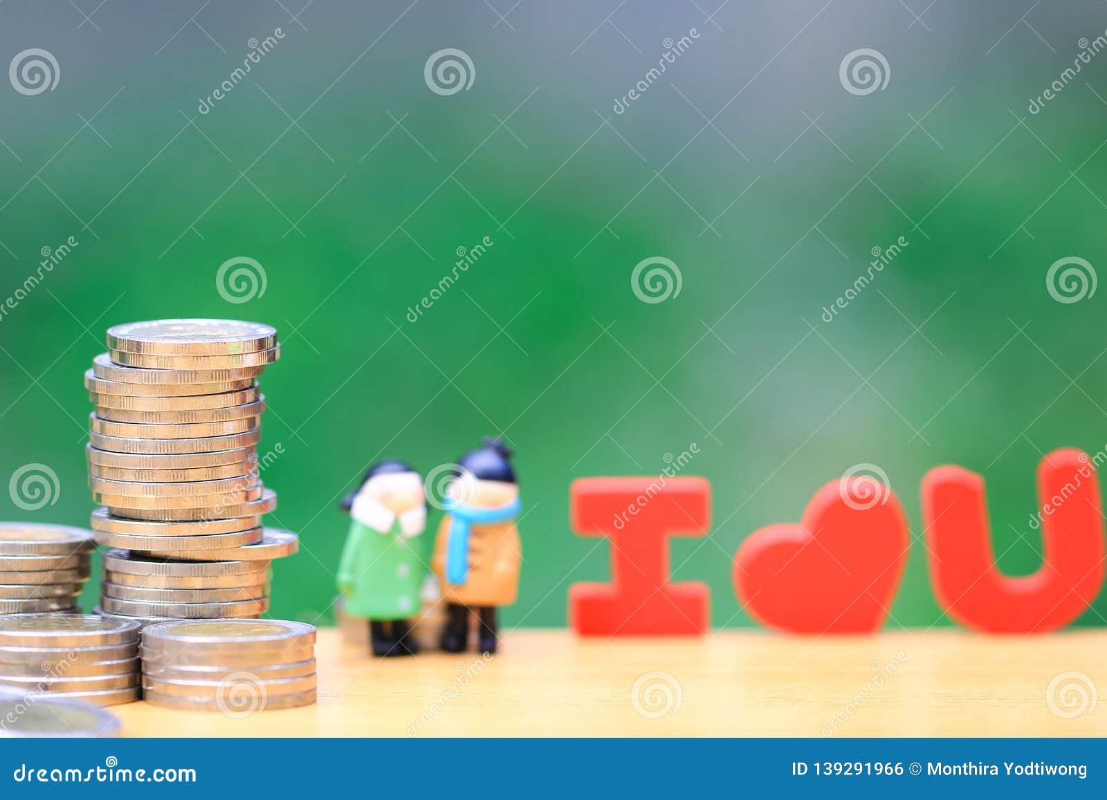 Pile d argent de pièces de monnaie et de position miniature de couples sur le fond vert naturel, économisant pour l amant ou la f