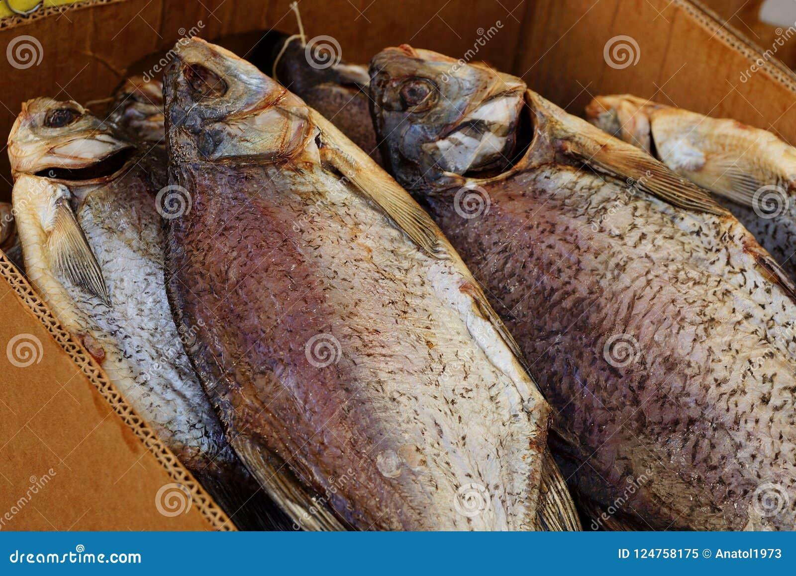 Pile de grands poissons secs dans une boîte de papier