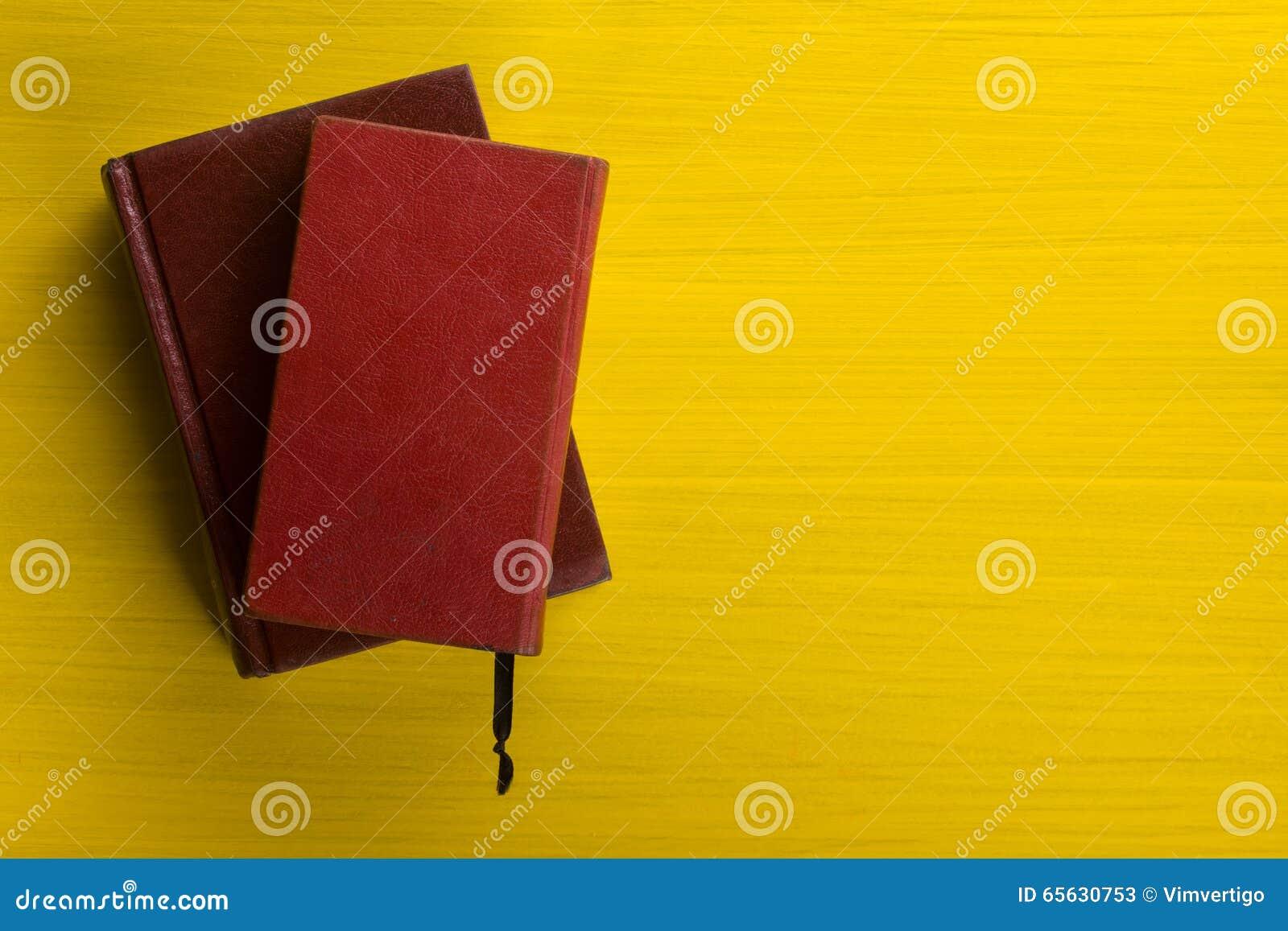 Pile de livres de livre cartonné, de journal intime sur la table en bois de plate-forme et de fond jaune De nouveau à l école Cop