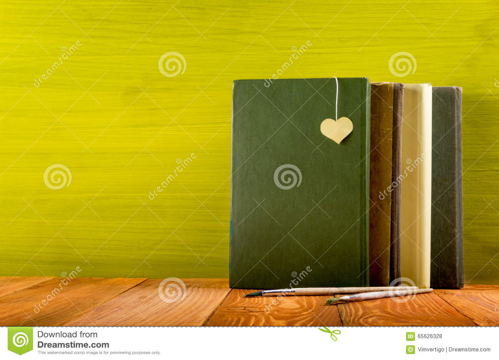Pile de livres de livre cartonné, de journal intime sur la table en bois de plate-forme et de fond vert De nouveau à l école Copi