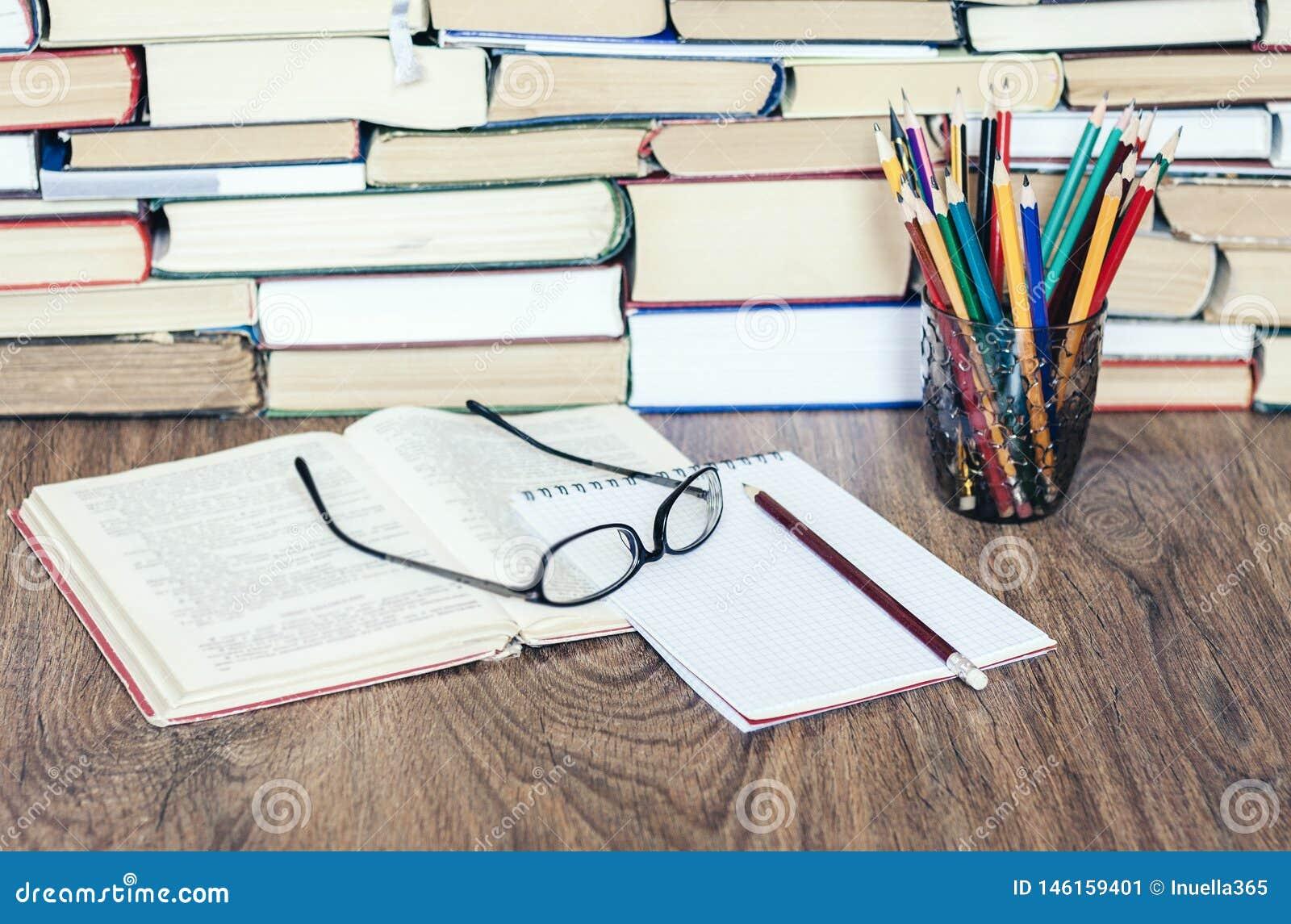 Pile de livres, de livres de livre cartonné sur la table en bois, de livre ouvert, de carnet et de verres, l espace de copie pour