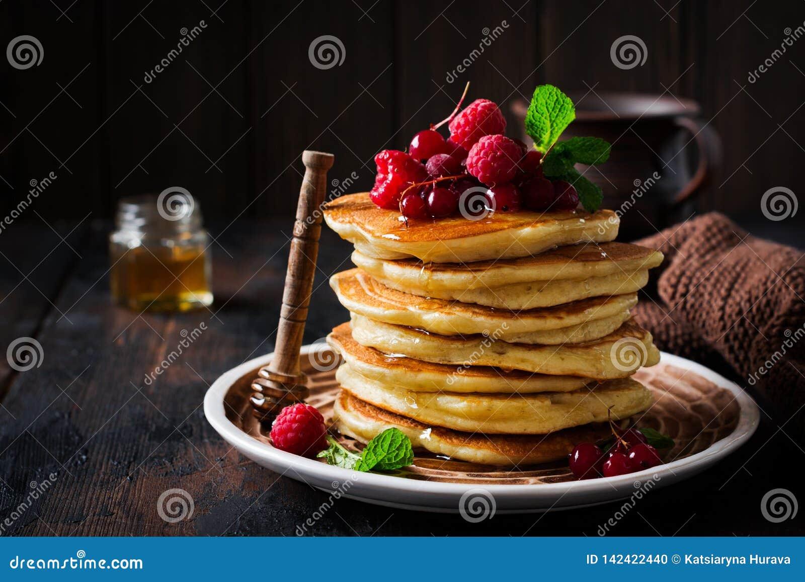 Pile de petites crêpes faites maison avec du miel, les framboises fraîches et les groseilles rouges sur un vieux fond en bois