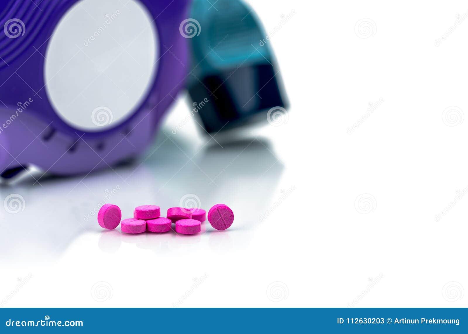 Pile de petites pilules roses rondes de comprimés sur le fond brouillé de l inhalateur d asthme un accuhaler