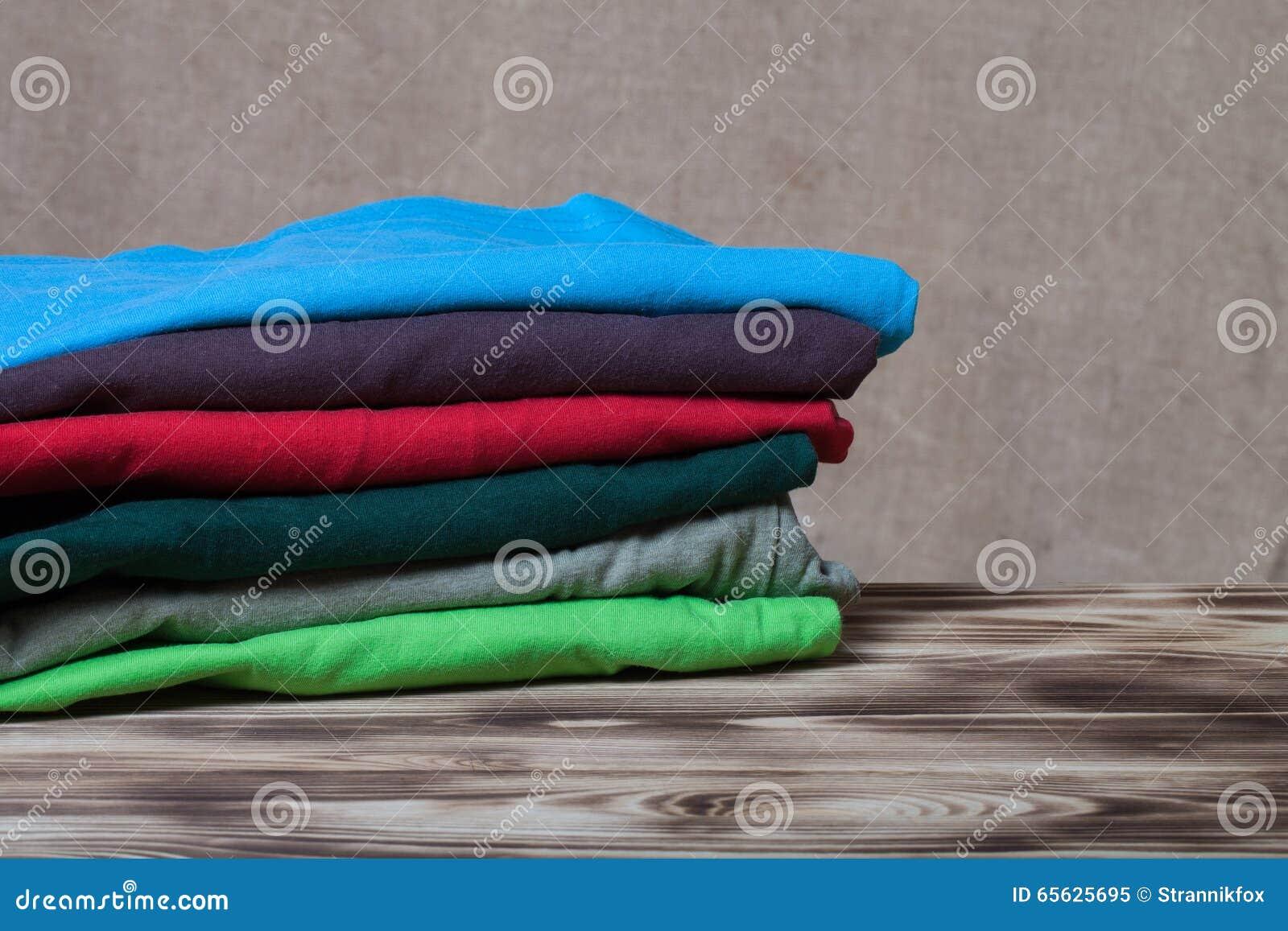 Pile de T-shirts sur la table en bois vis-à-vis d un Ba defocused de toile de jute