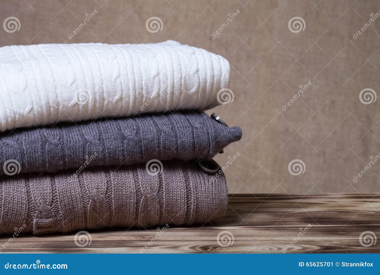 Pile de vêtements tricotés sur la table en bois vis-à-vis d un Bu defocused