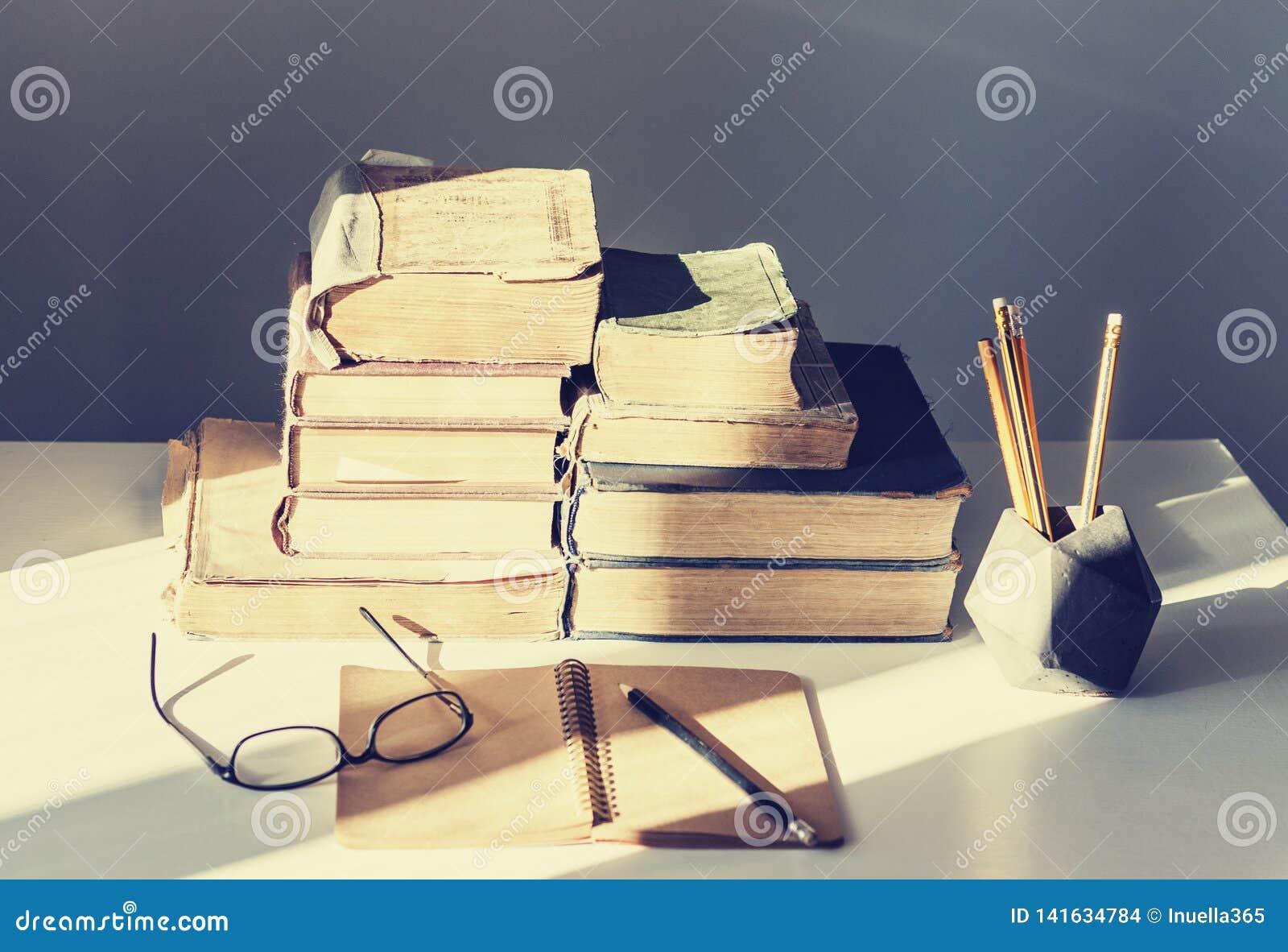 Pile de vieux livres, de manuel, de verres et de crayons à l arrière-plan de bureau pour le rétro concept d éducation