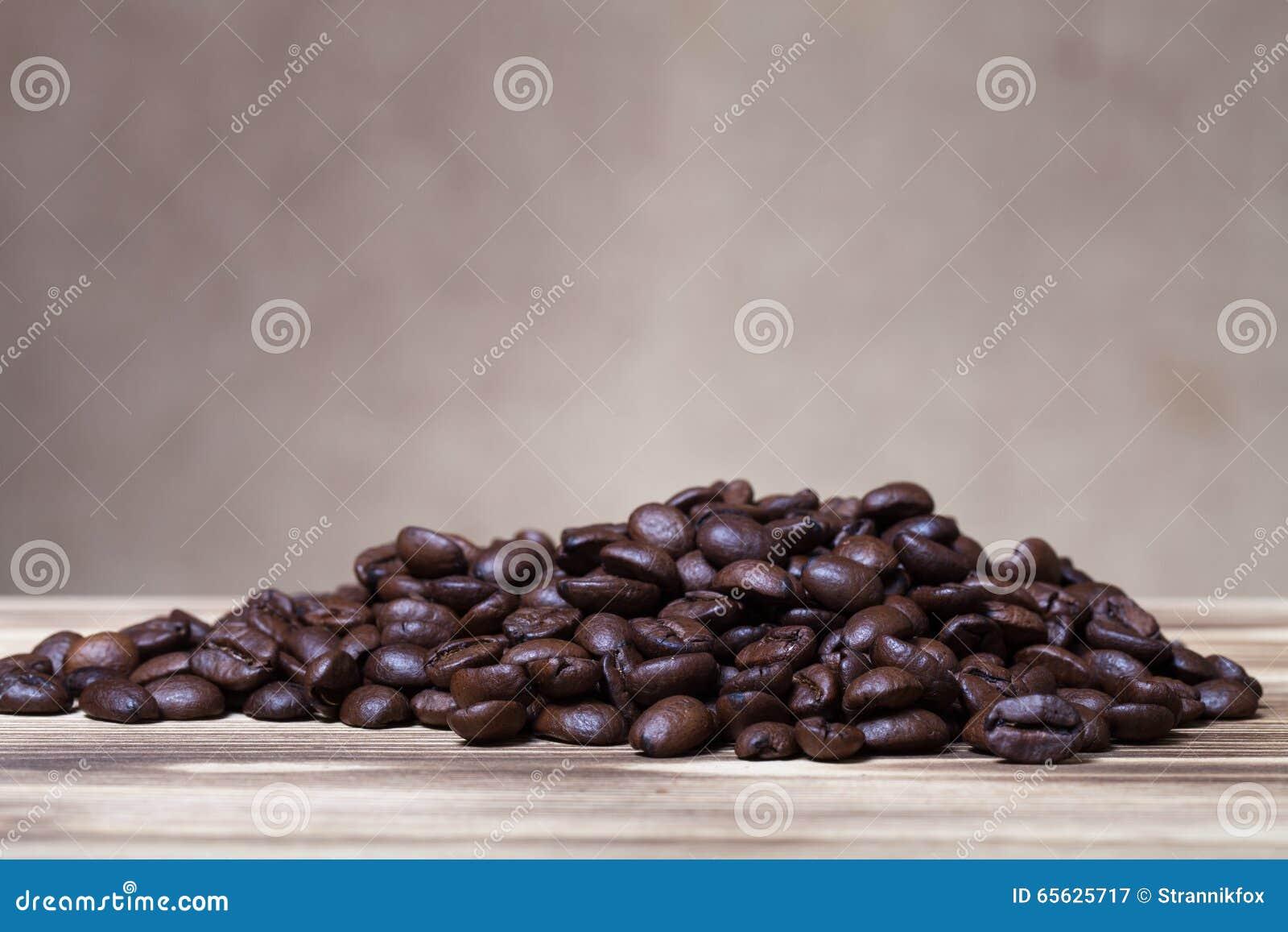 Pile des grains de café sur la table en bois vis-à-vis d une toile de jute defocused