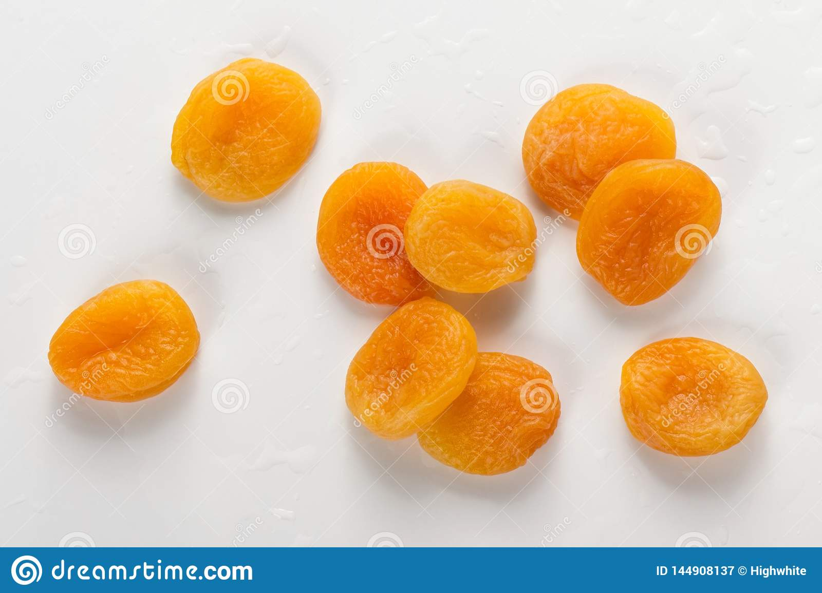 Pile of fresh dried apricots on white background, washed fruits in water , macro photo close up, top view.