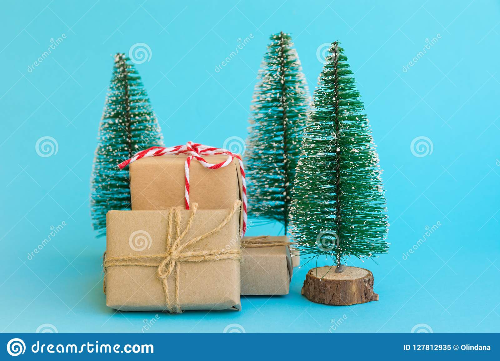 Pile of gift boxes wrapped in craft paper tied with twine red white ribbon Christmas trees on mint blue background. New Year