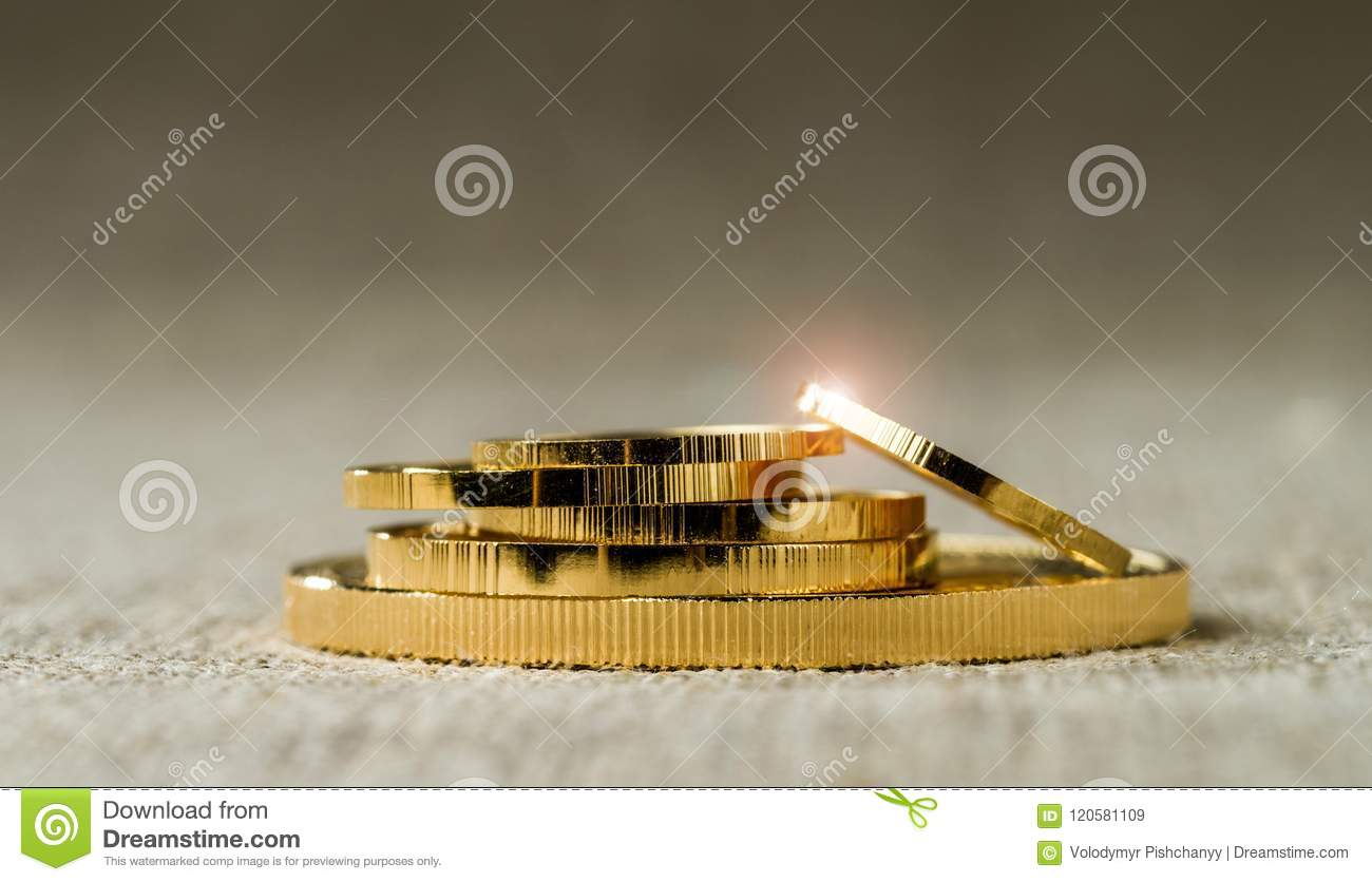 A pile of gold coins of various sizes on a neutral blurred background
