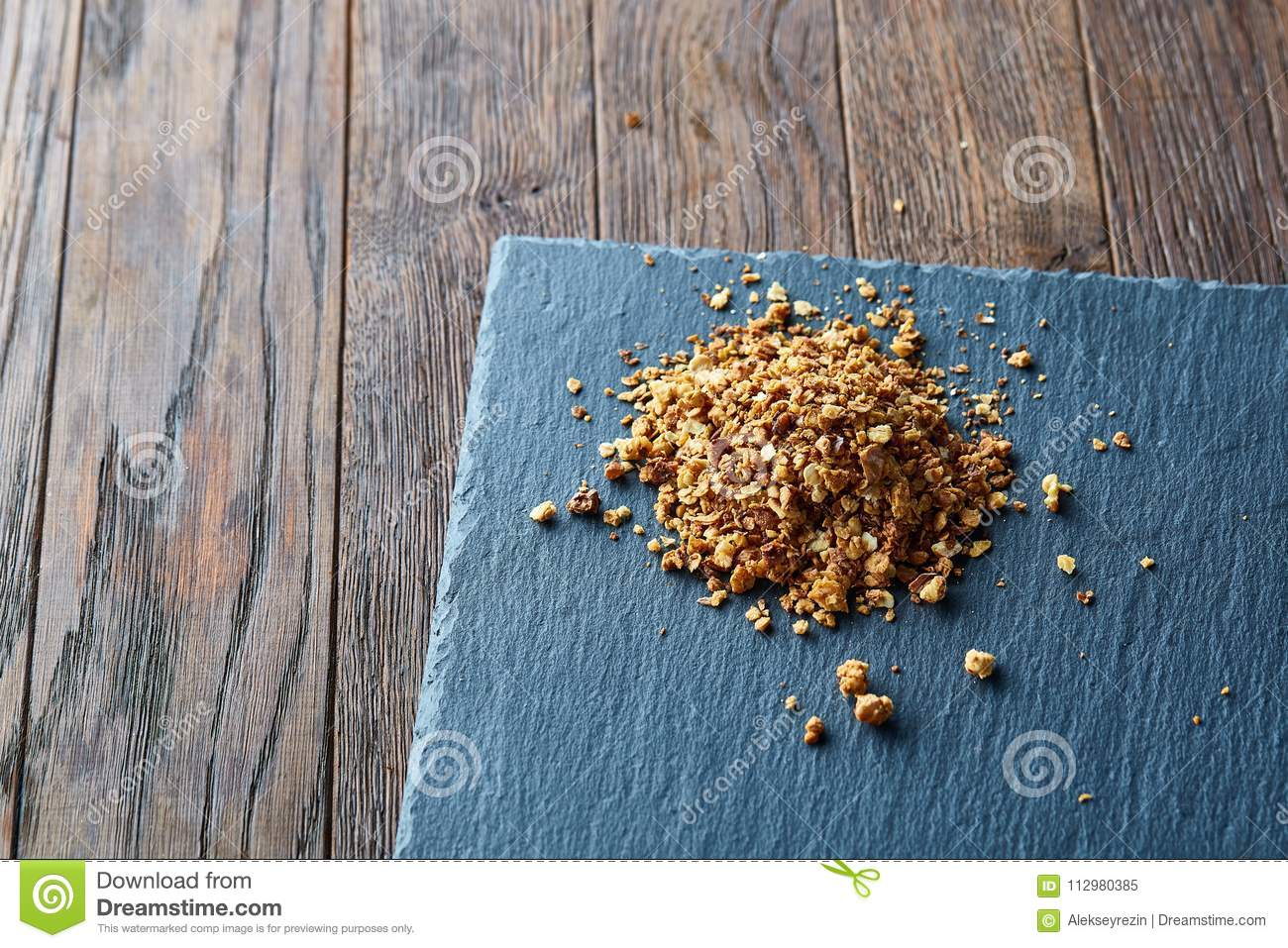 Pile of healthy granola on black stony board over vintage wooden background, top view, close-up, selective focus