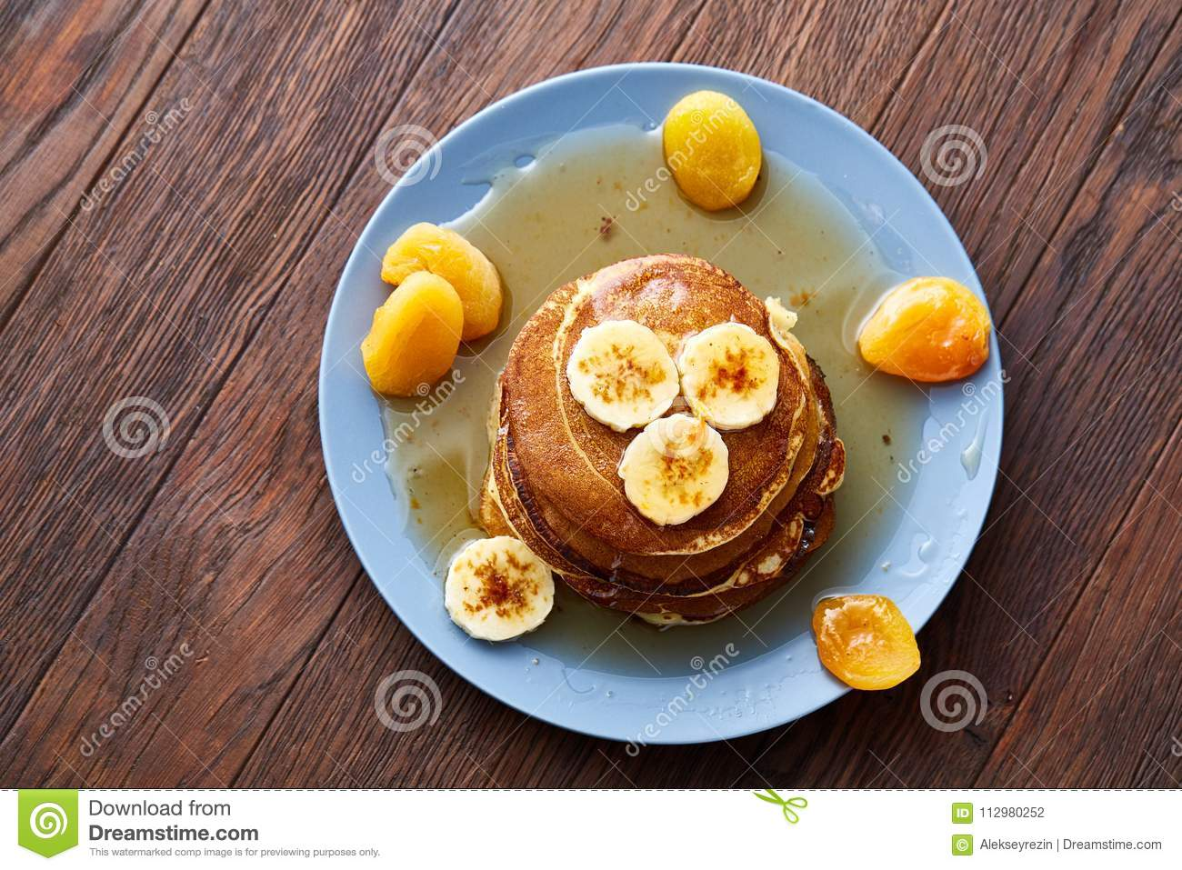 Pile of homemade pancakes with honey and walnuts on rustic wooden background, selective focus