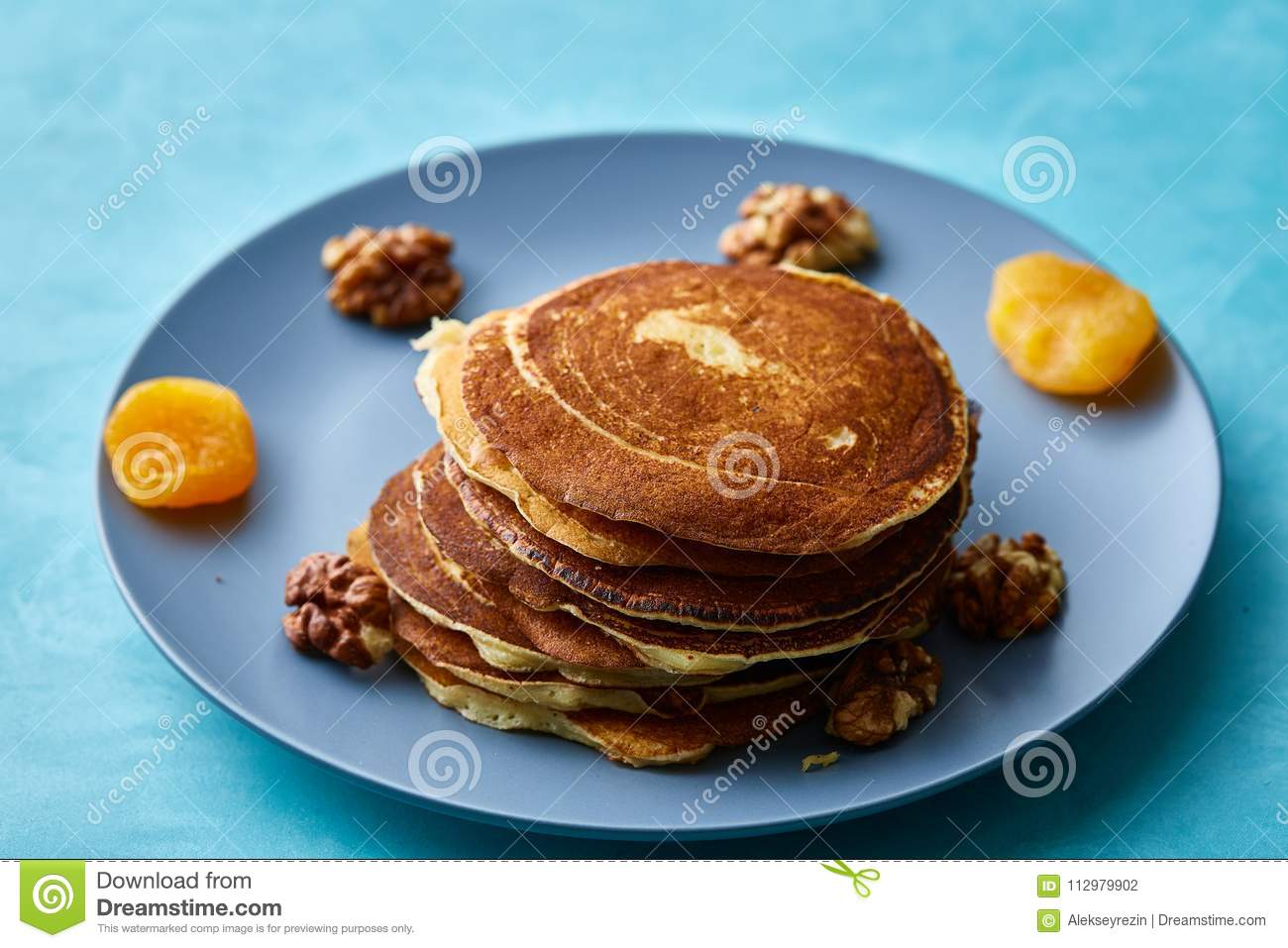 Pile of homemade pancakes with walnuts on blueish plate over blue background, selective focus