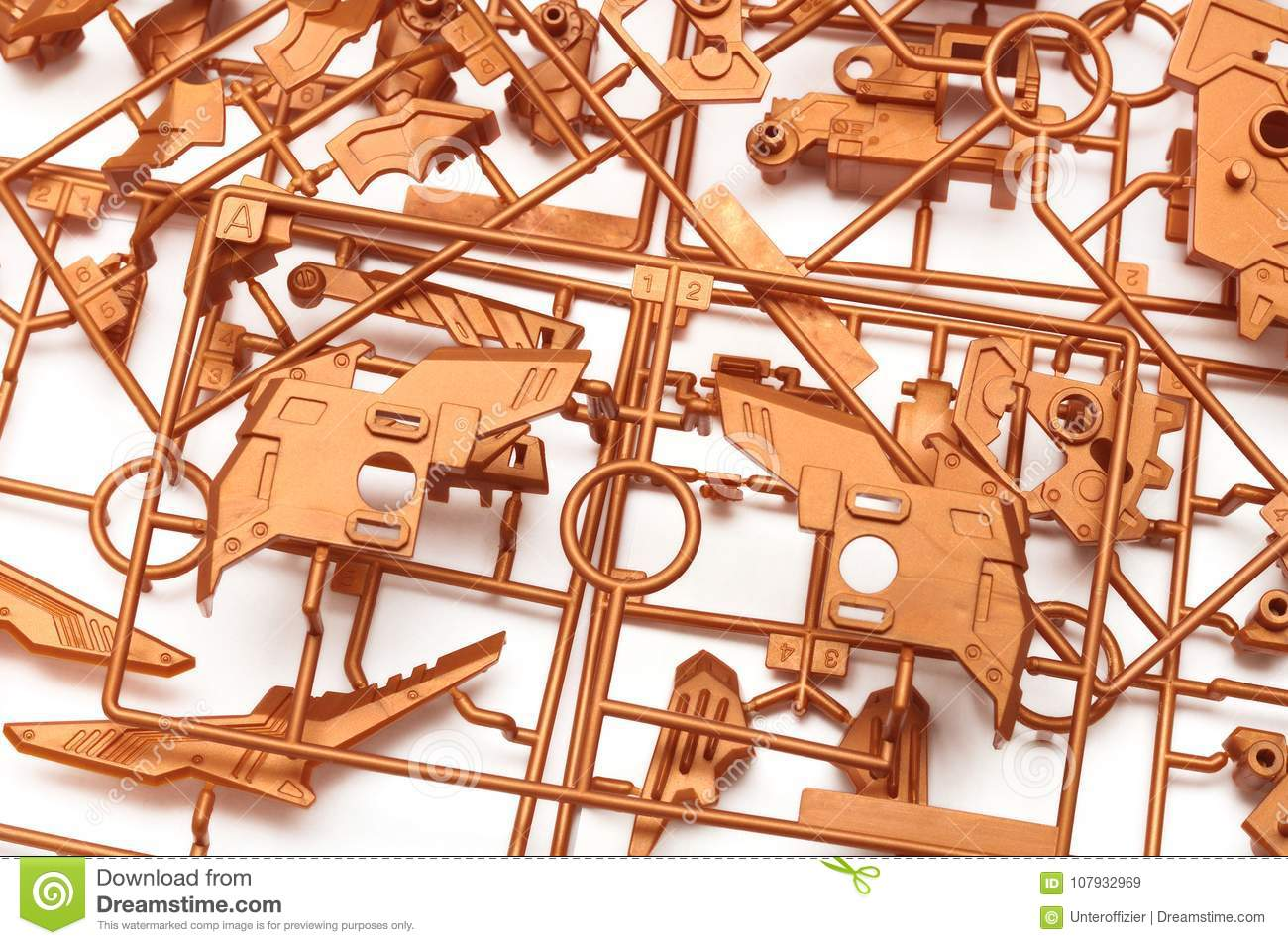 A Pile Of Metallic Orange Plastic Scale Model Kit Set With