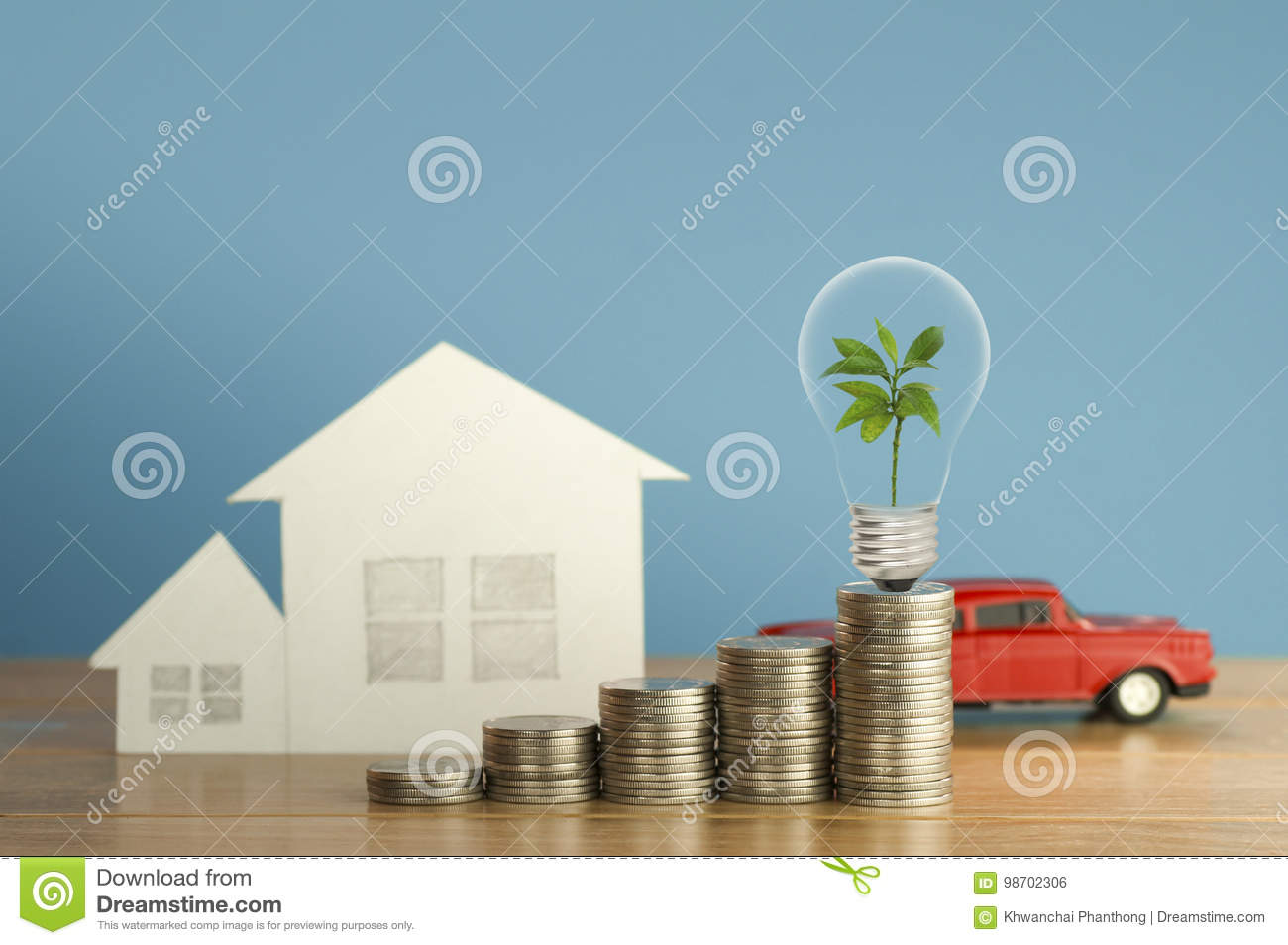 Pile of money coins with small green tree, light bulb, toy car and paper home,on wood and soft blue background, concept