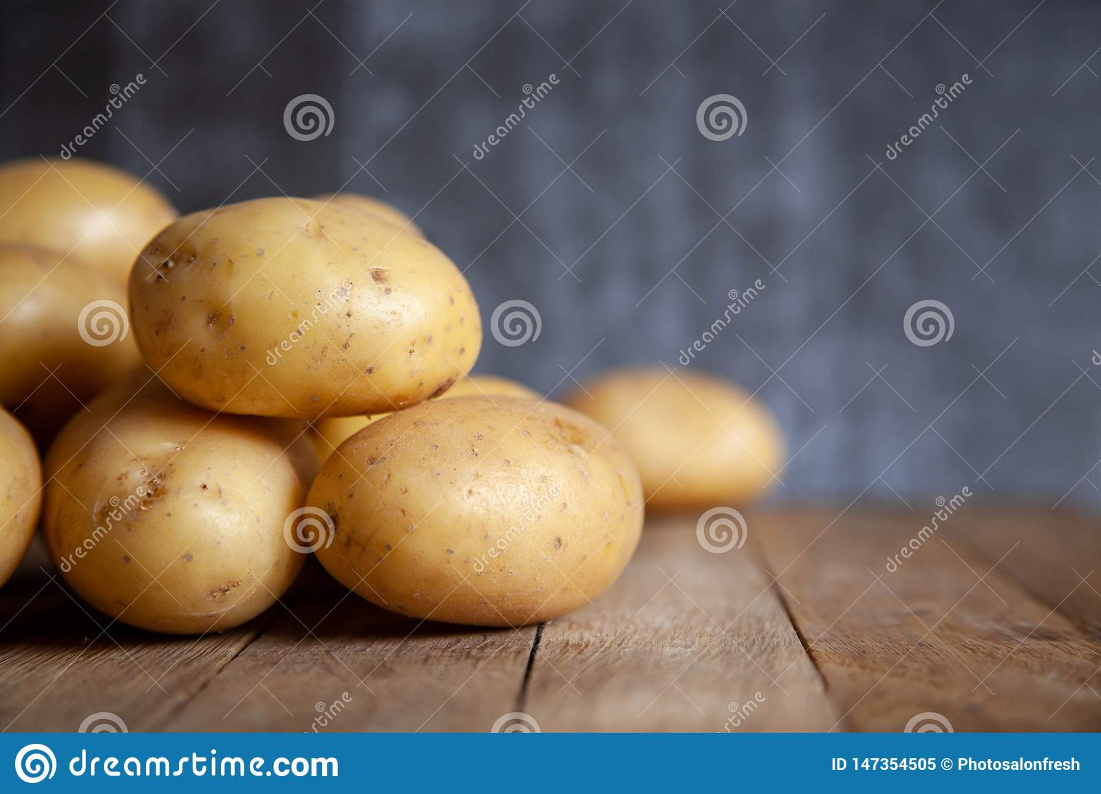 Pile of potatoes on old wooden table.
