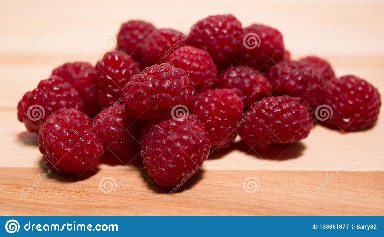 Pile of raspberries on a natural wooden background.