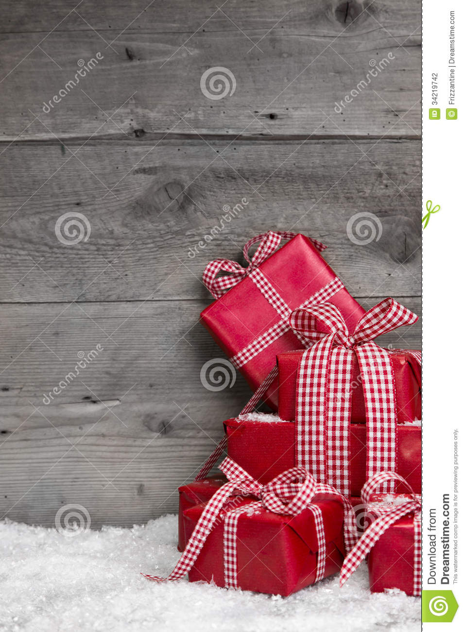 pile of red christmas gifts  snow on grey wooden