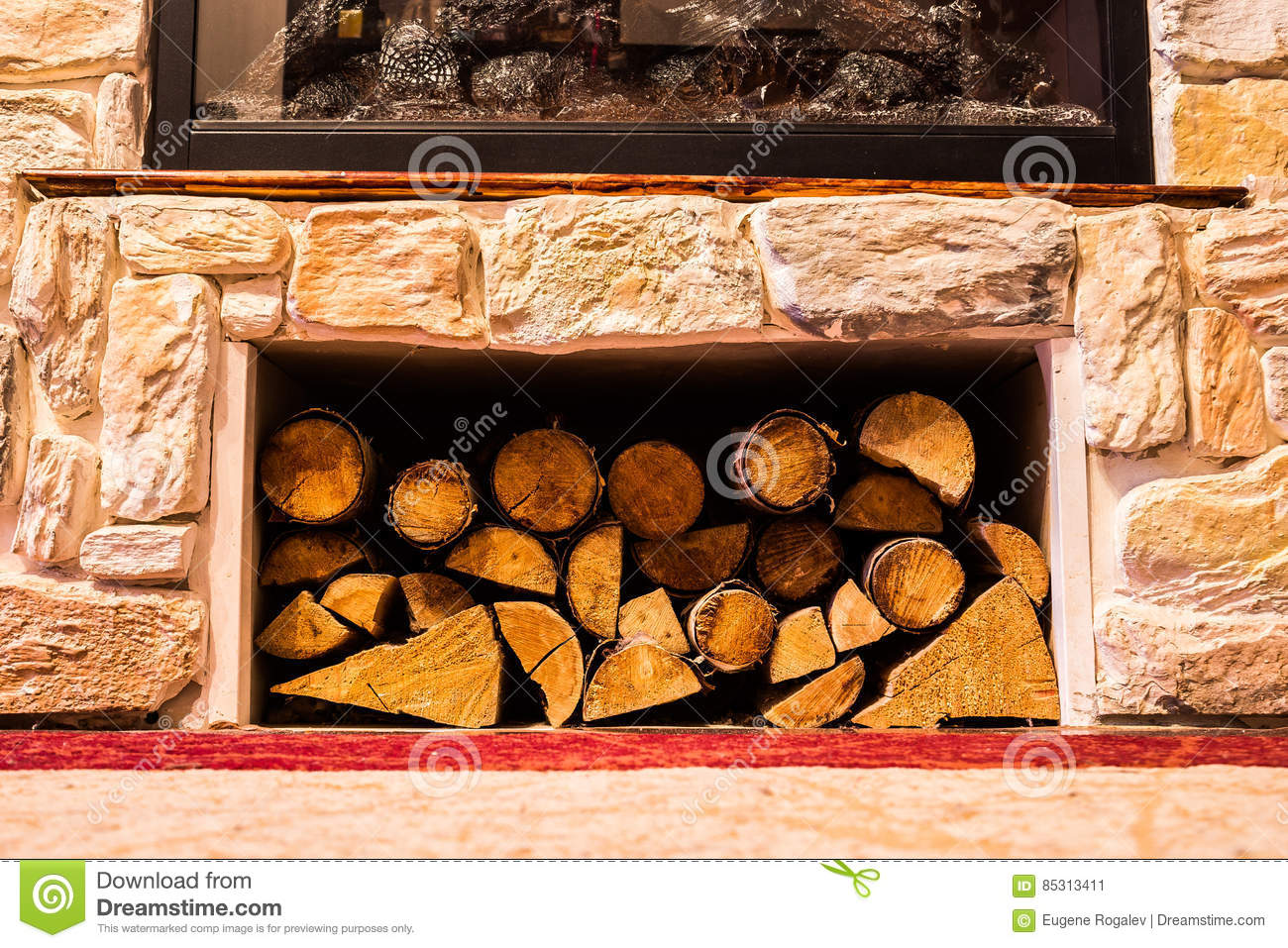 Pile of small logs under a fireplace