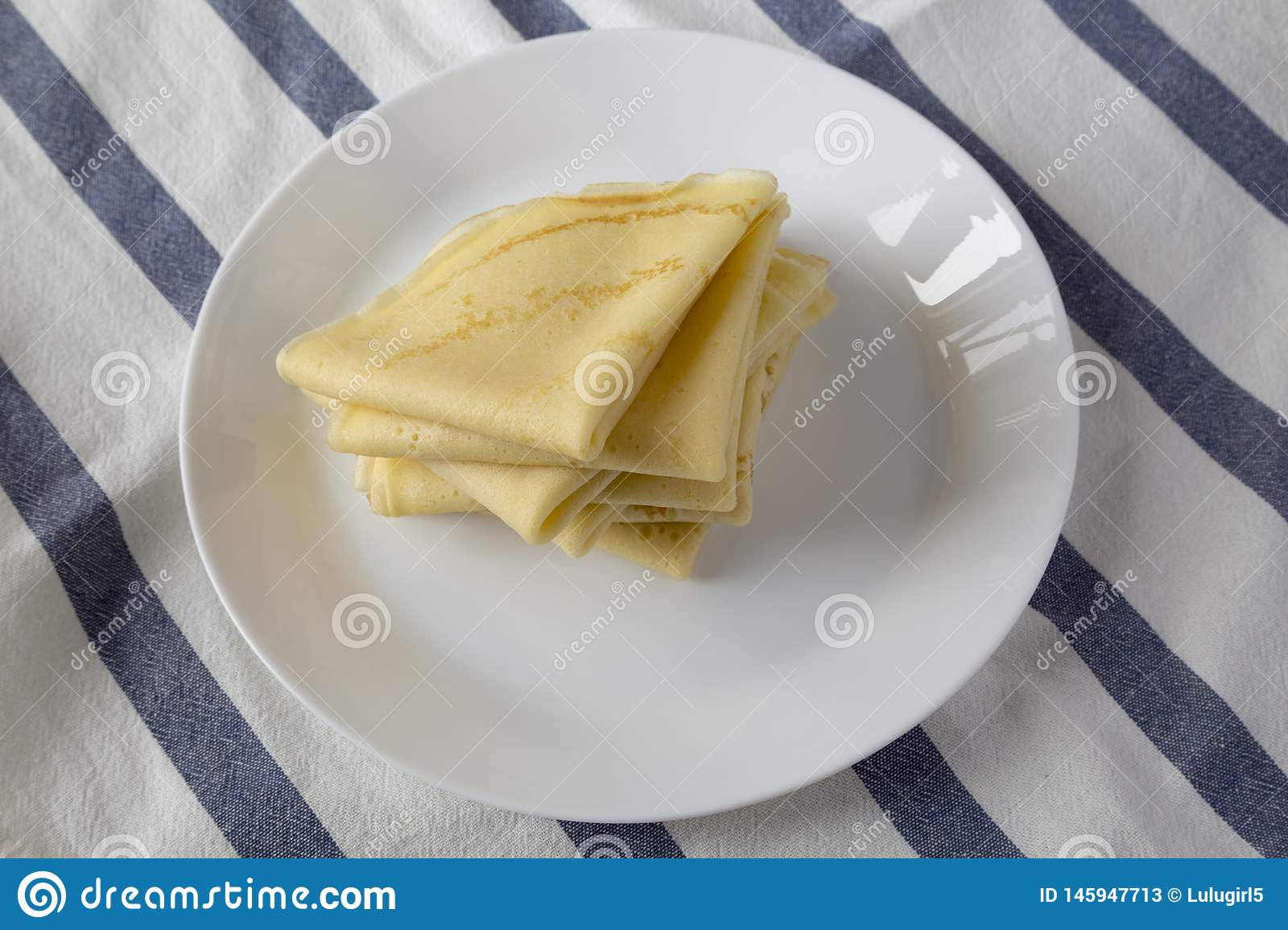 Pile of tasty blini on a white plate, side view. Close-up