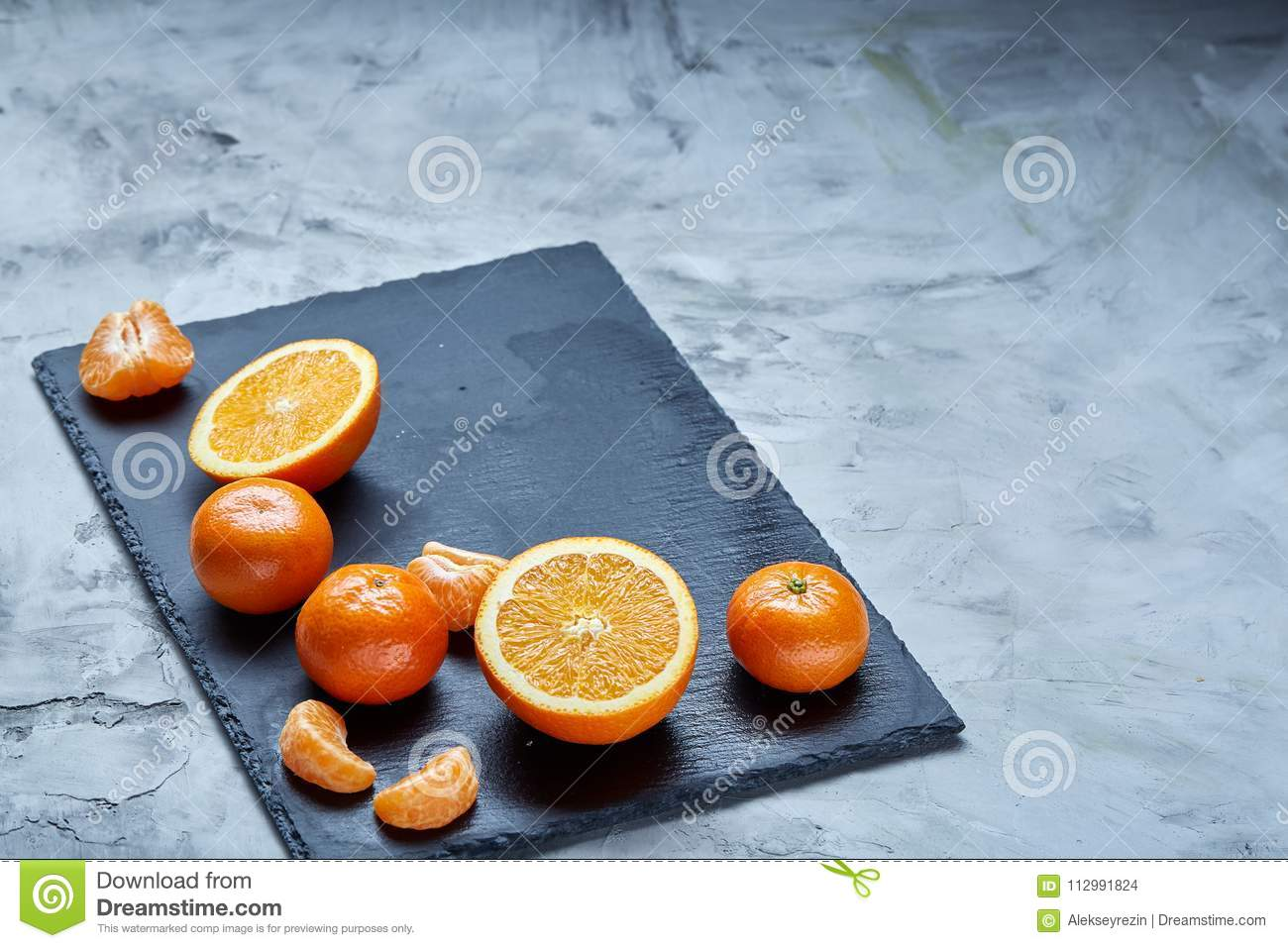 Pile of whole and half cut fresh tangerine and orange on cutting board, close-up